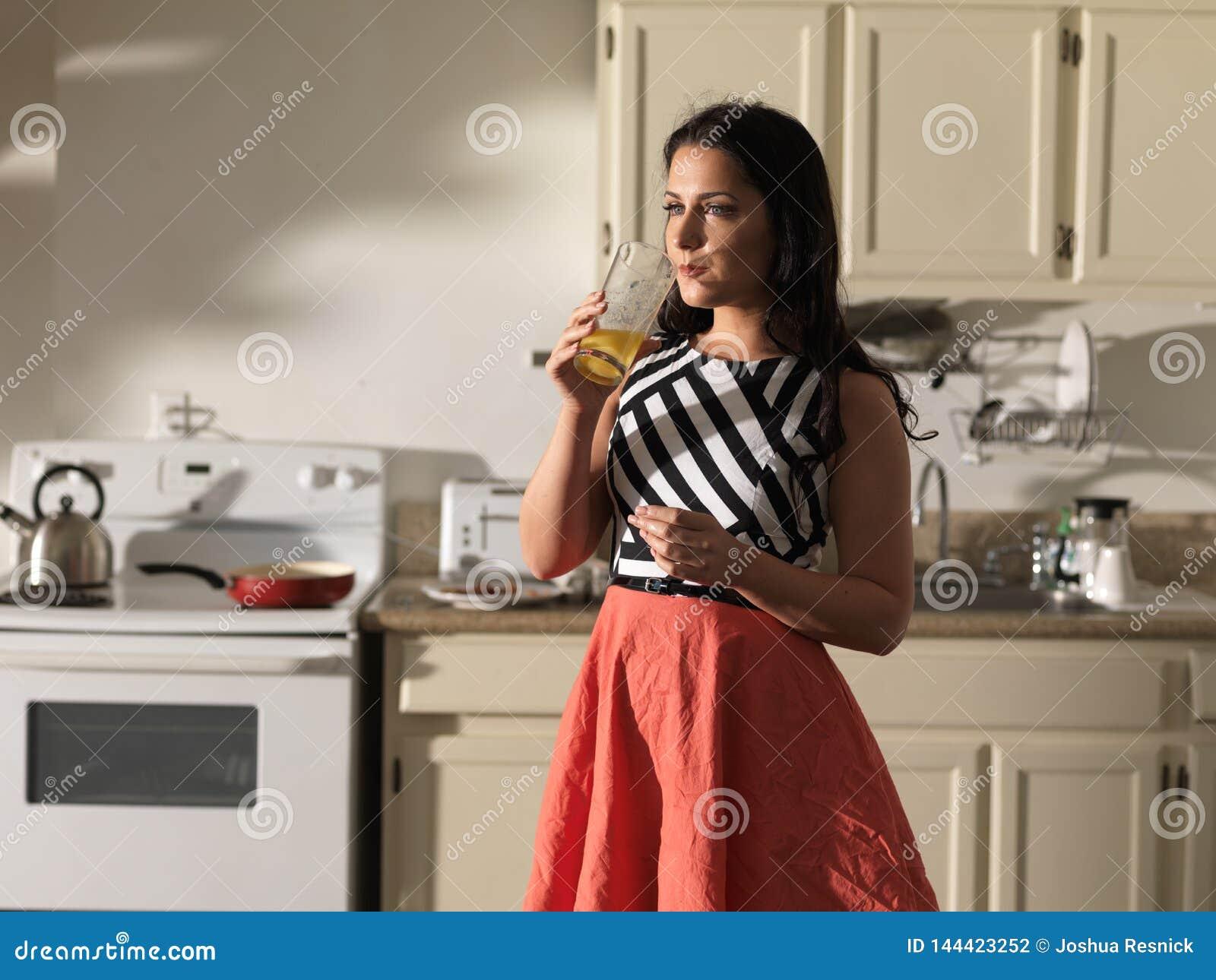 Kvinna som dricker orange fruktsaft i kök som bär den retro klänningen
