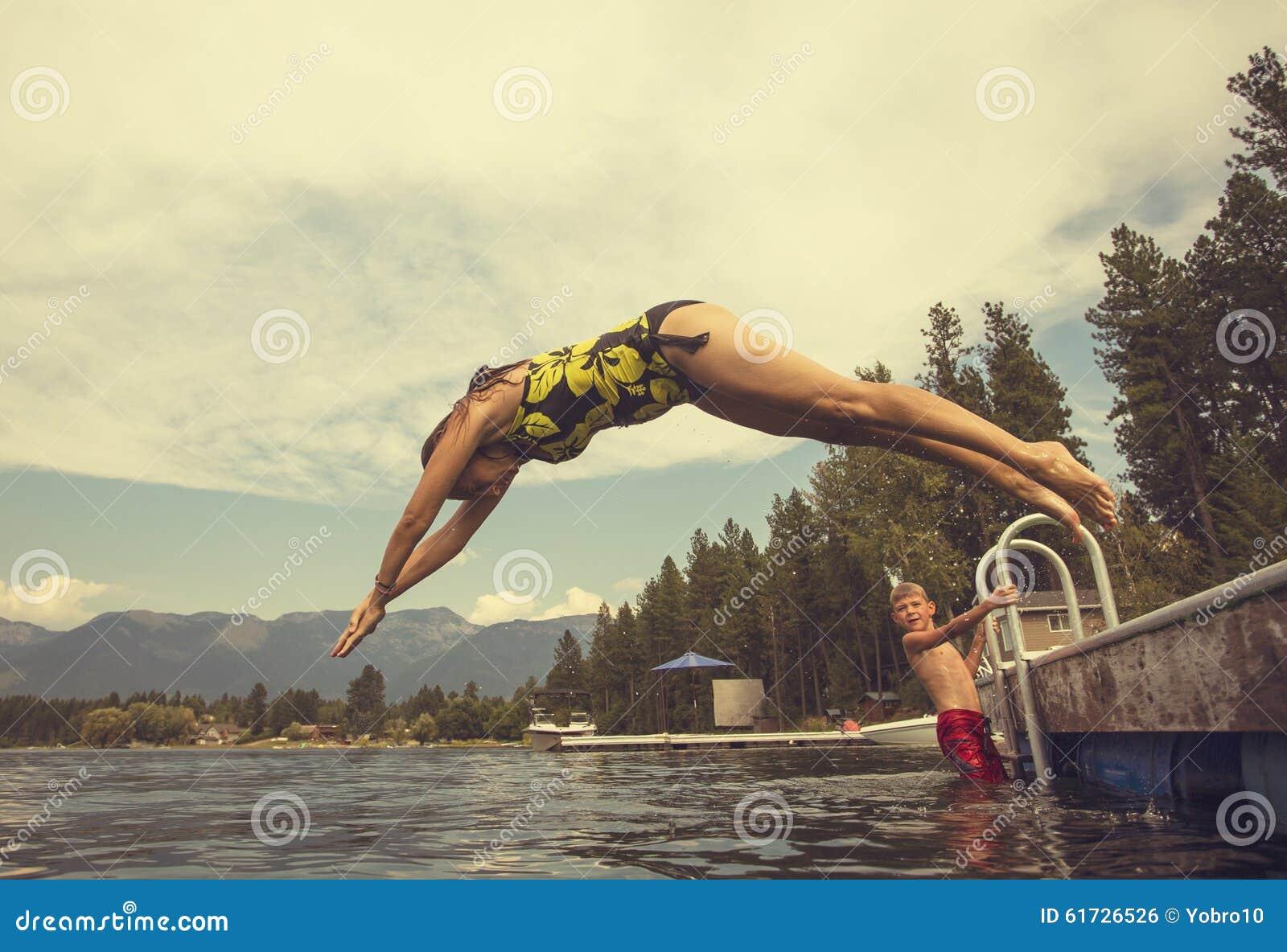 Kvinna som dyker av skeppsdockan av sjön medan på sommarsemester