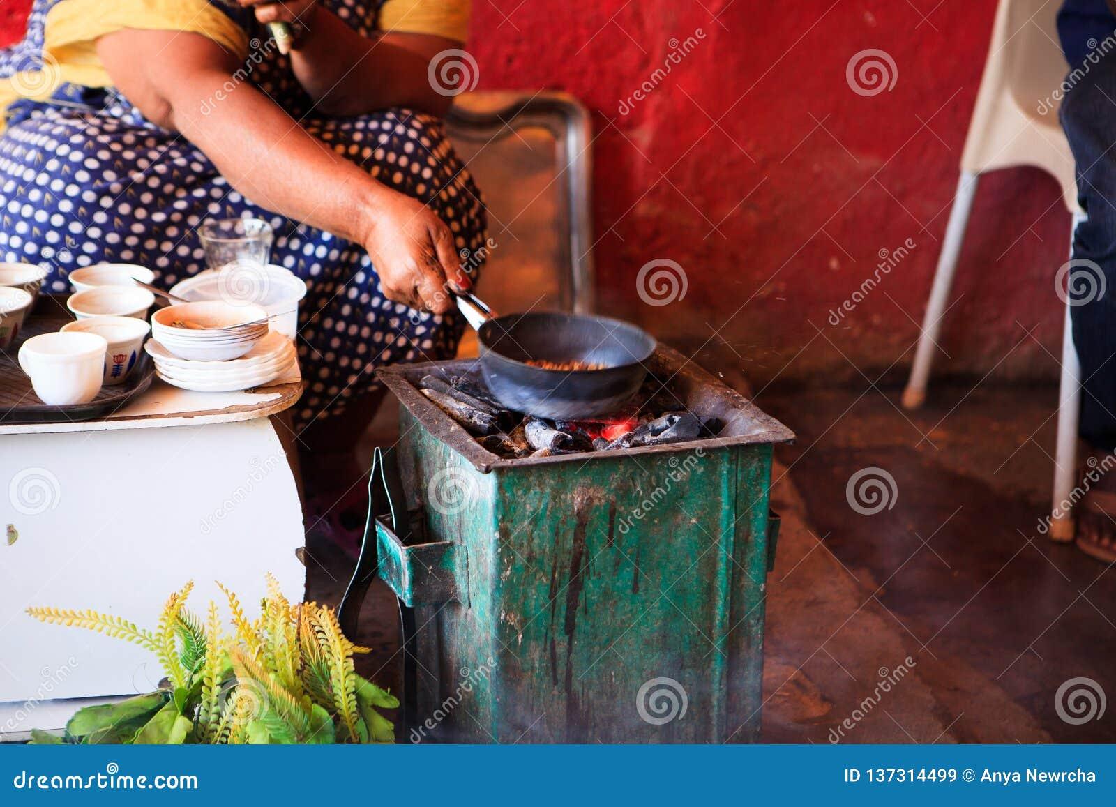 Kvinna som förbereder kaffe för turister i en traditionell väg