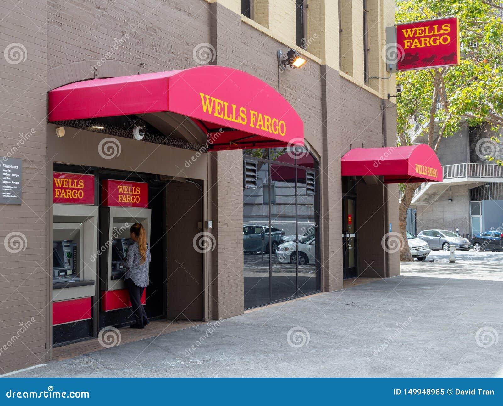 Kvinna som förutom använder läge för filial för Wells Fargo ATM maskin