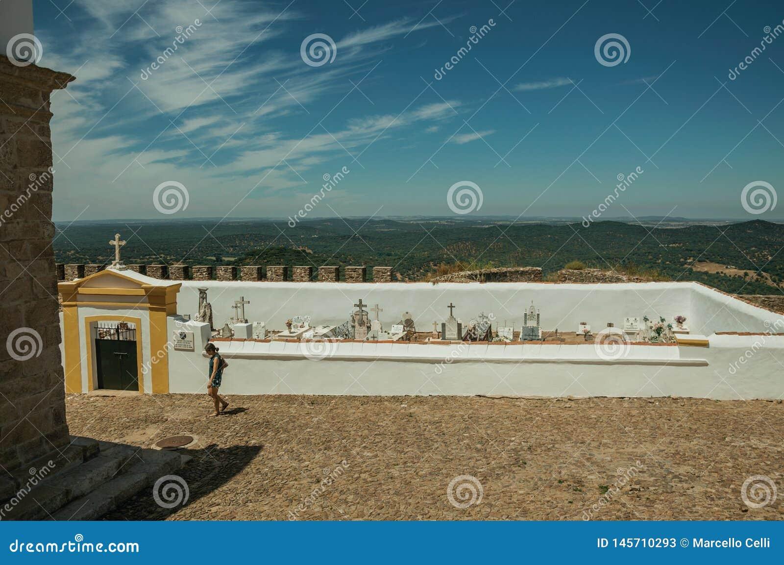 Kvinna som framme går av kyrkogård på Evoramonte