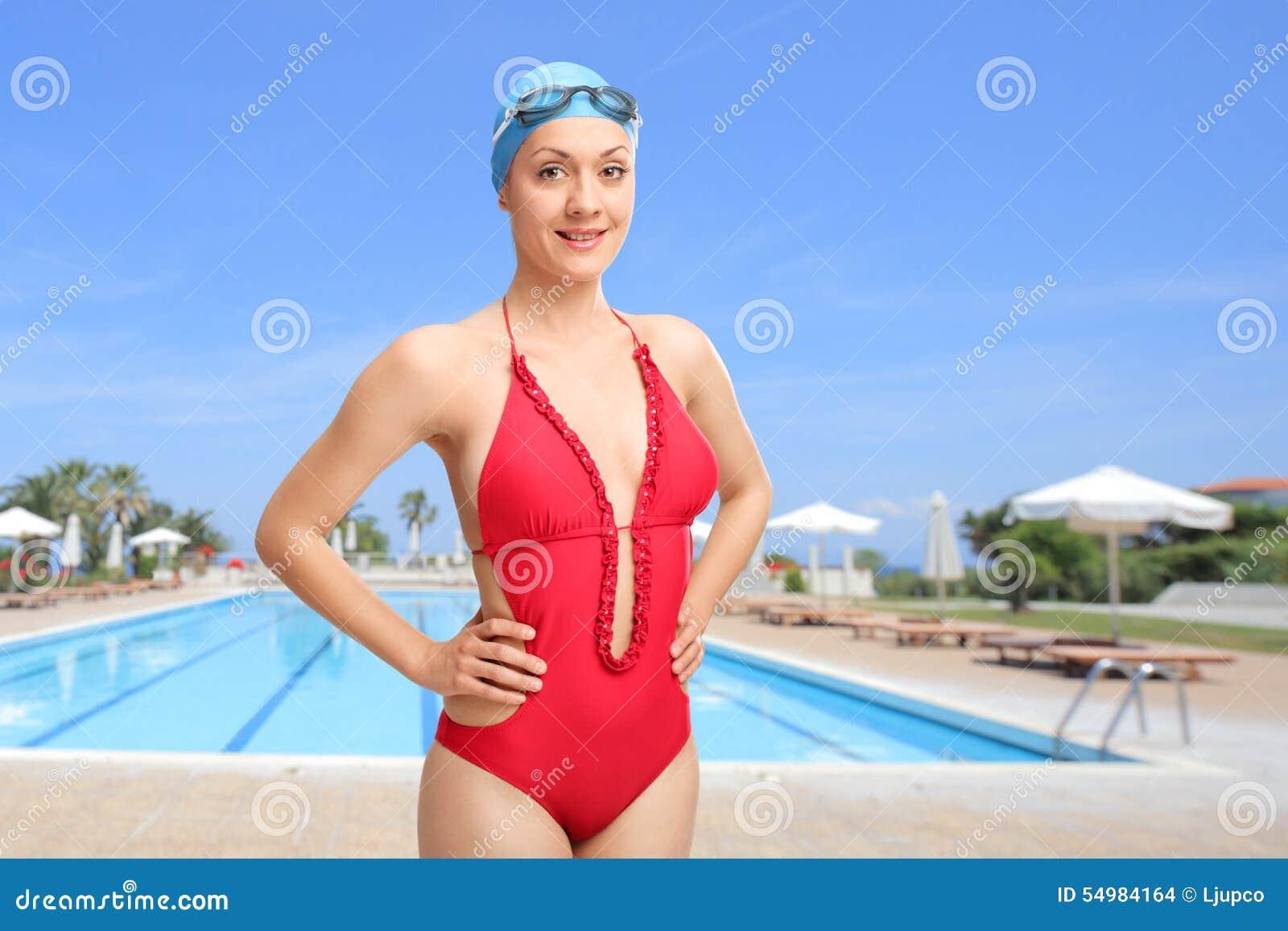 Kvinna som framme poserar av en simbassäng
