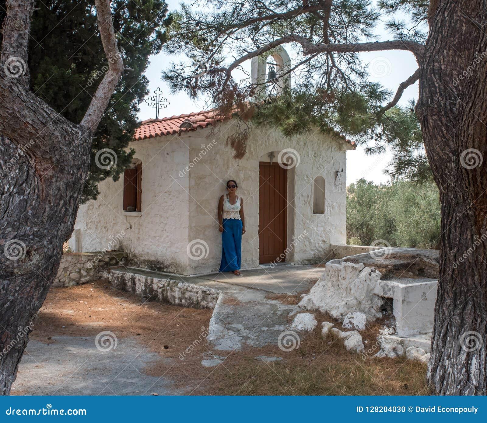 Kvinna som framme står av kyrka