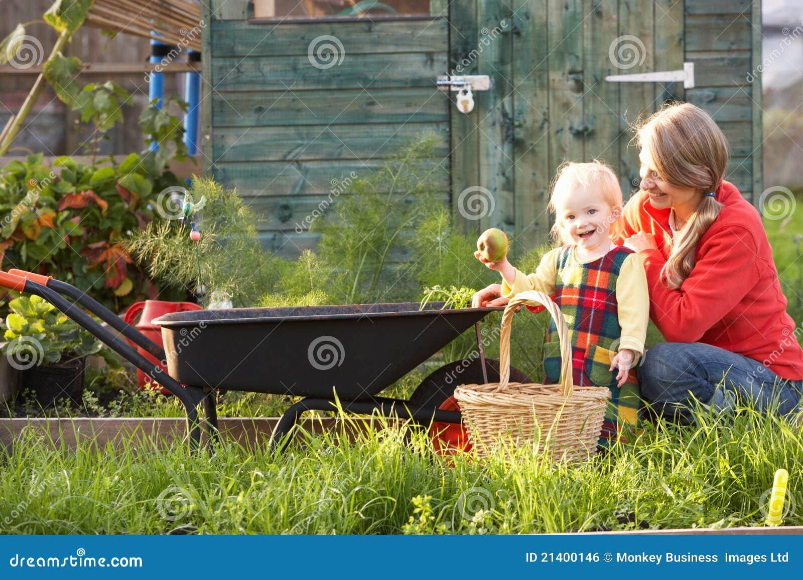 Kvinna som fungerar på odlingslott med barnet