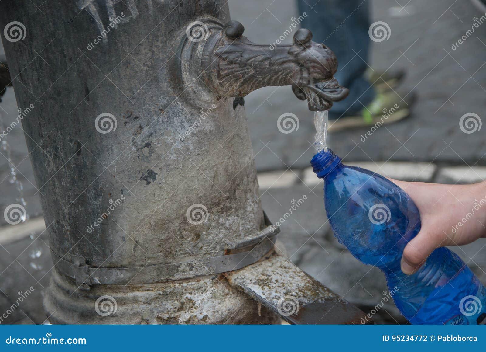 Kvinna som fyller en flaska med drickbart vatten i en offentlig springbrunn av Rome
