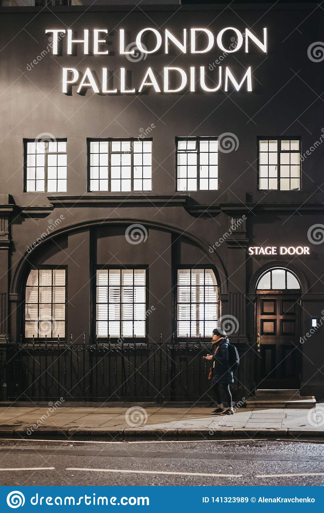 Kvinna som går förbi etappingången till den London Palladiumteatern, London, UK