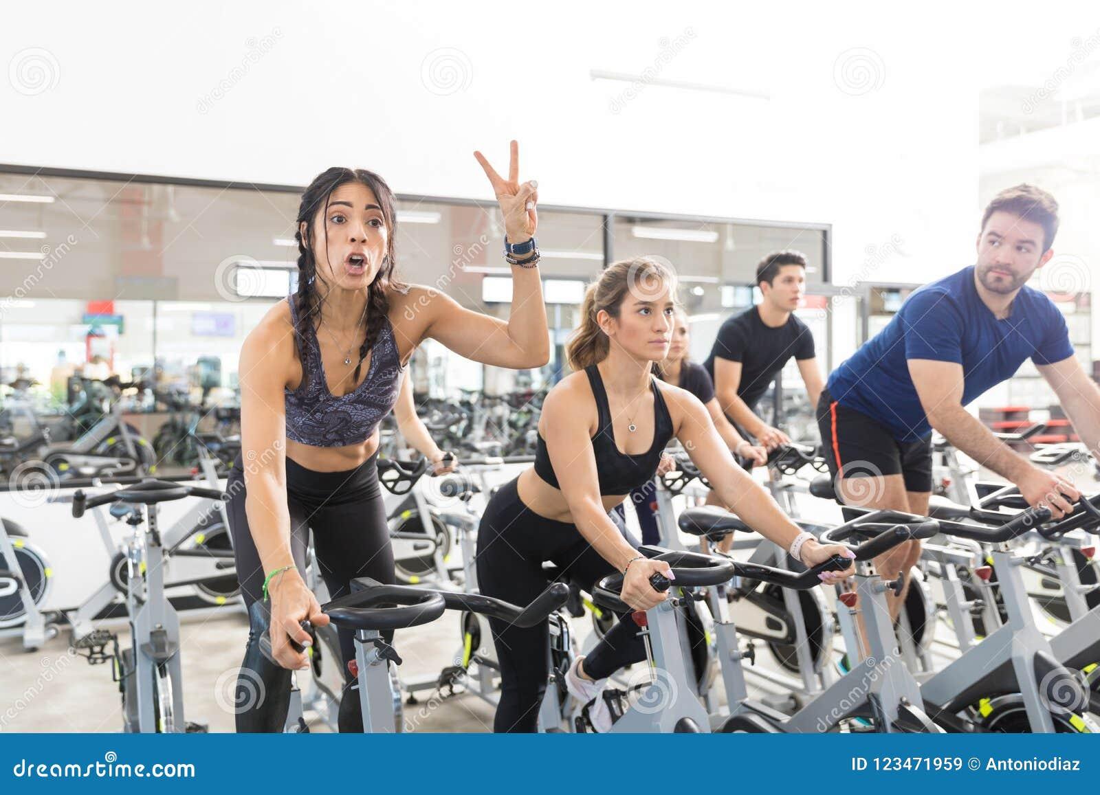 Kvinna som gör en gest den Victory While Exercising On Spinning cykeln i idrottshall