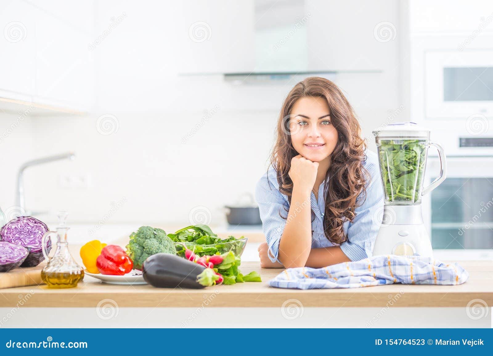 Kvinna som gör grönsaksoppa eller smoothies med blandaren i hennes kök Ung lycklig kvinna som förbereder den sunda drinken med sp