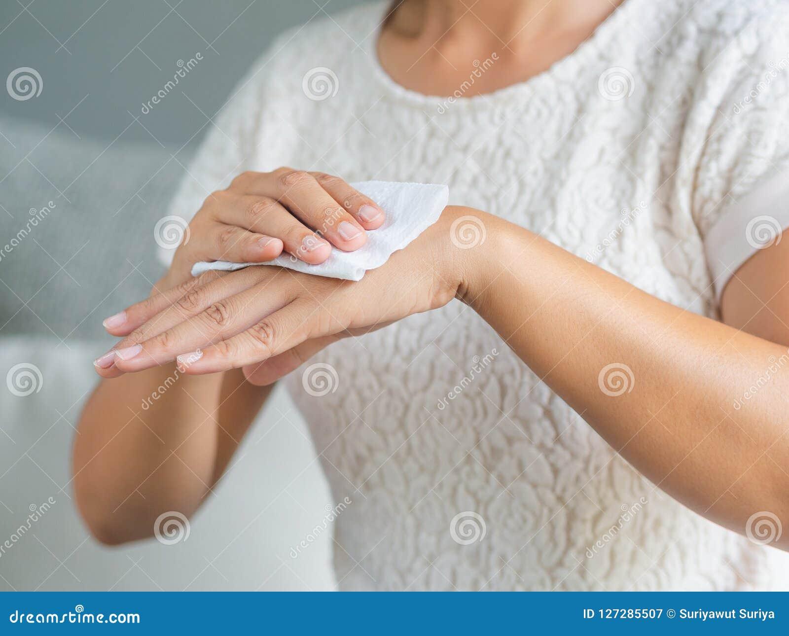 Kvinna som gör ren hennes händer med ett silkespapper Sjukvård och läkarundersökning c