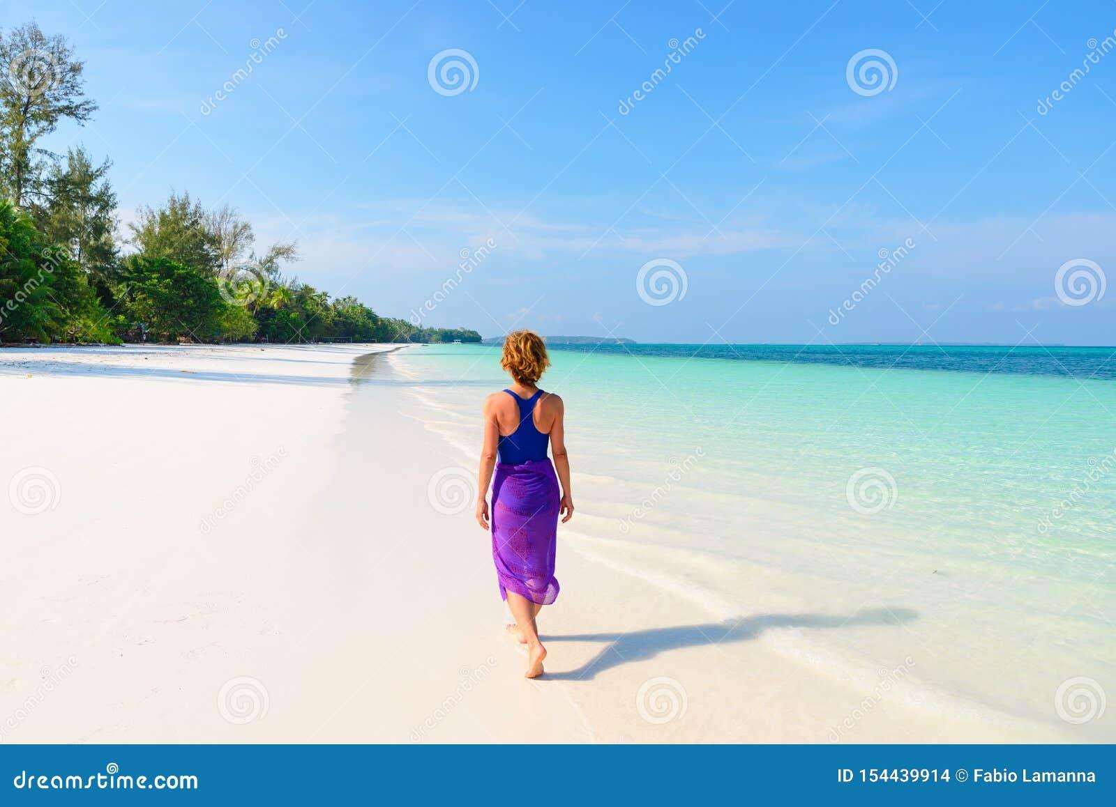 Kvinna som g?r p? den tropiska stranden För sandstrand för bakre sikt folk för karibiskt hav för vatten för vit turkos trasparent