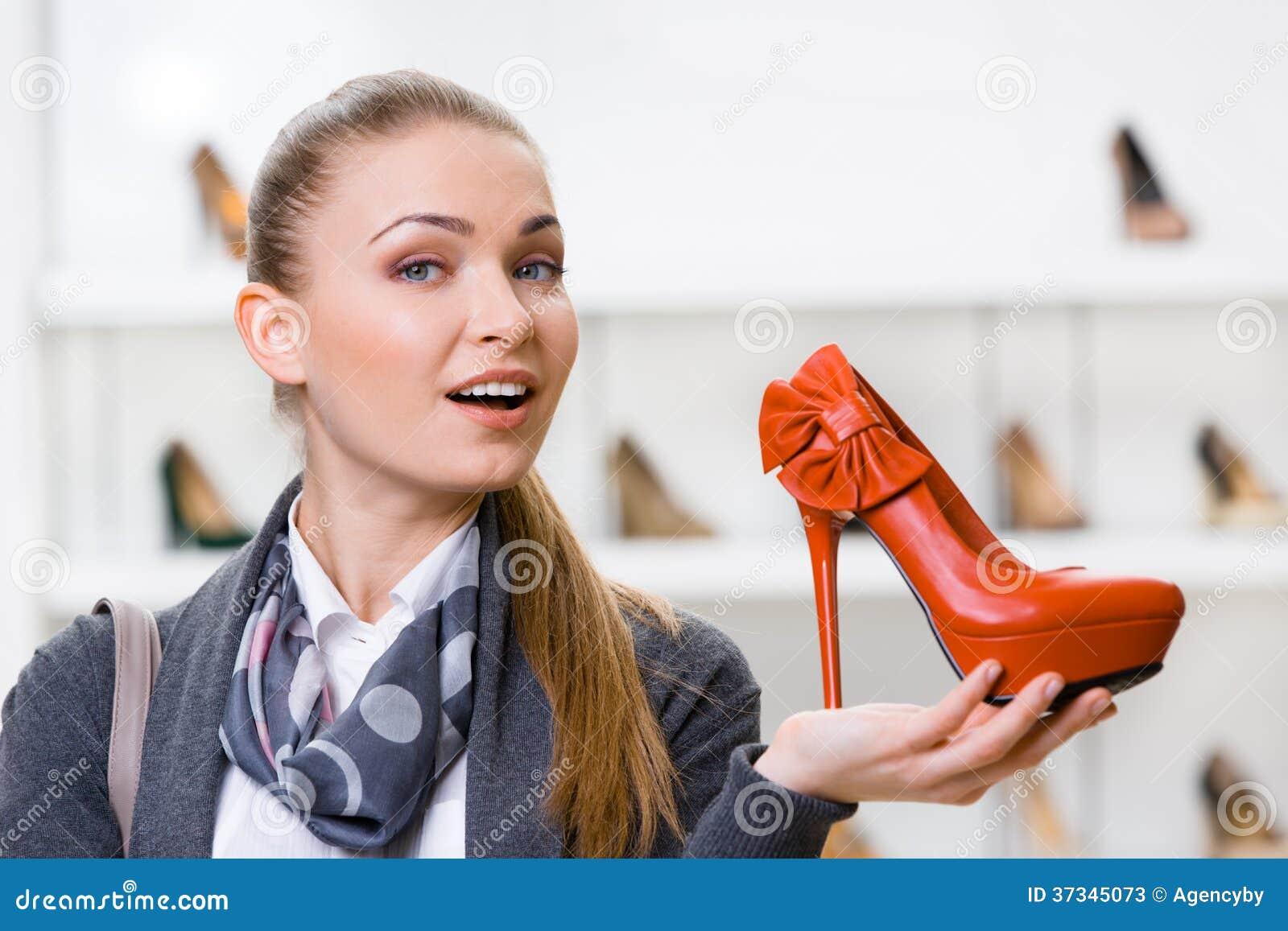 Kvinna som håller den orange läderpumpen