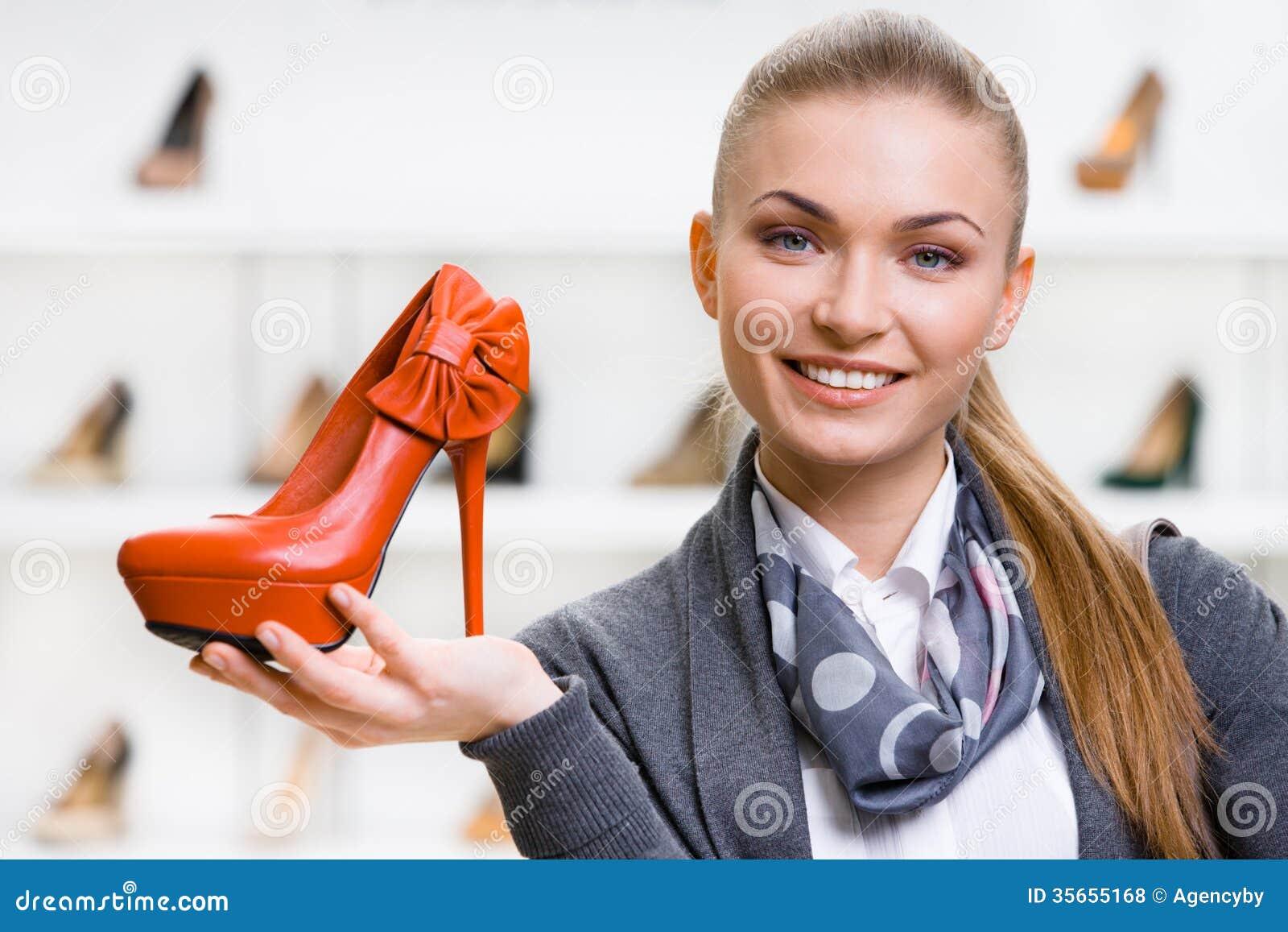 Kvinna som håller den orange läderskon
