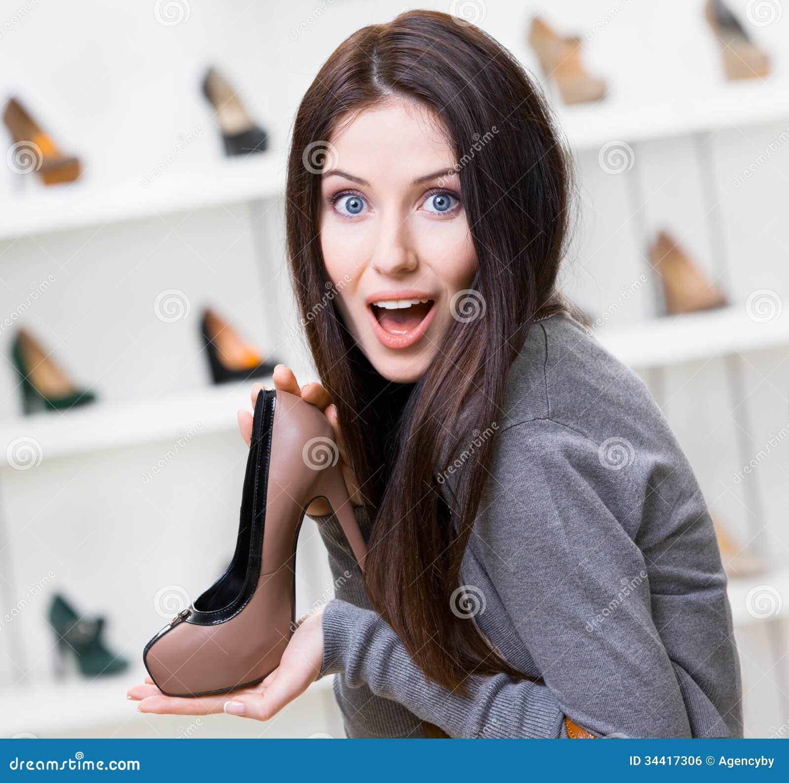 Kvinna som håller denfärgade stilfulla skon
