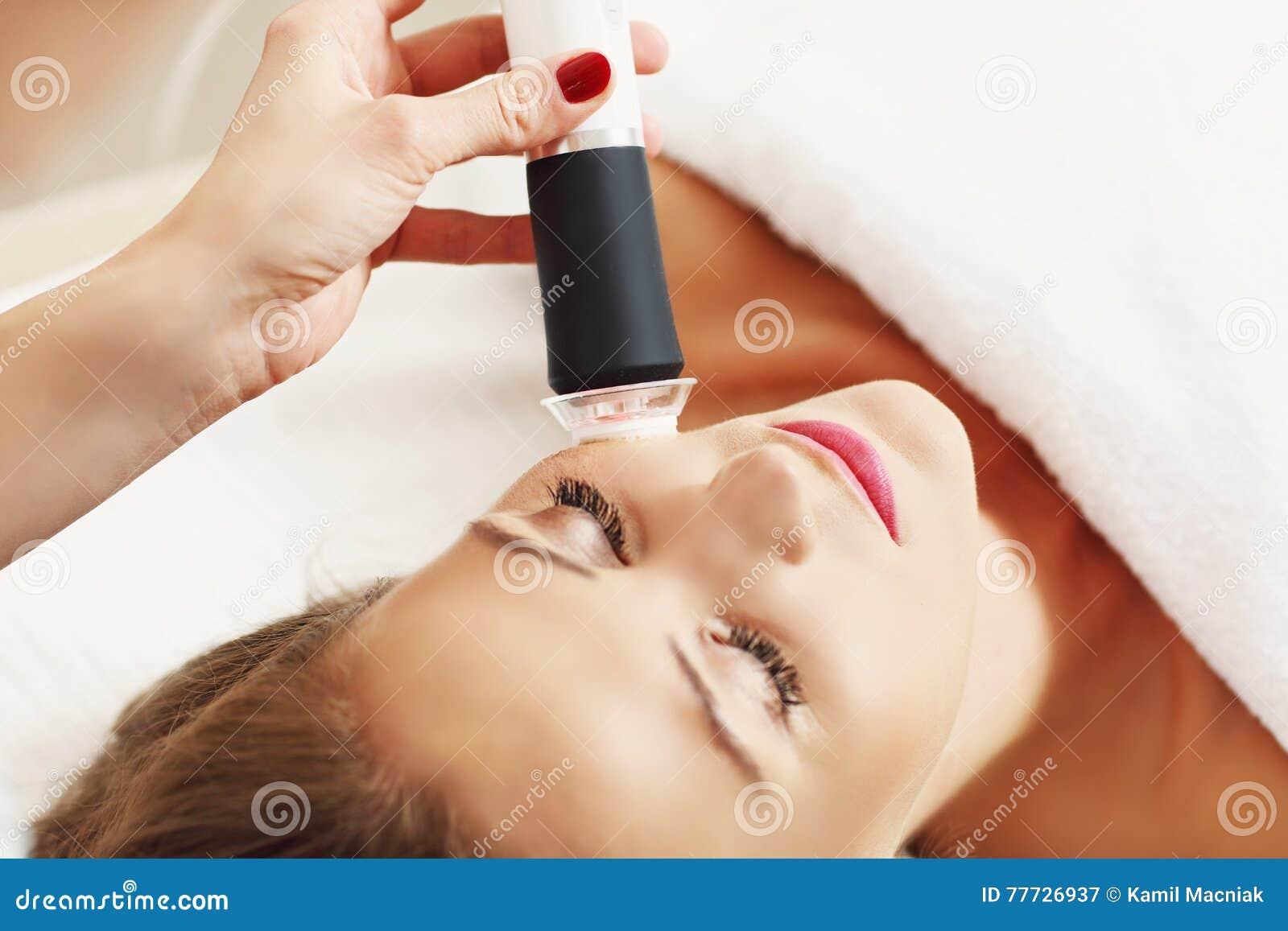 Kvinna som har ansikts- skalning i skönhetsalong