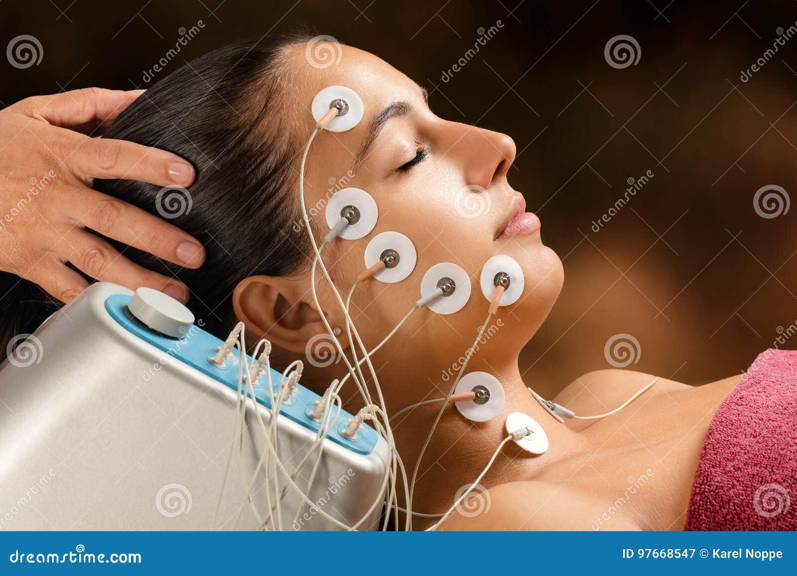 Kvinna som har behandling för framsidaelevator med bottenläget - frekvenselektroder