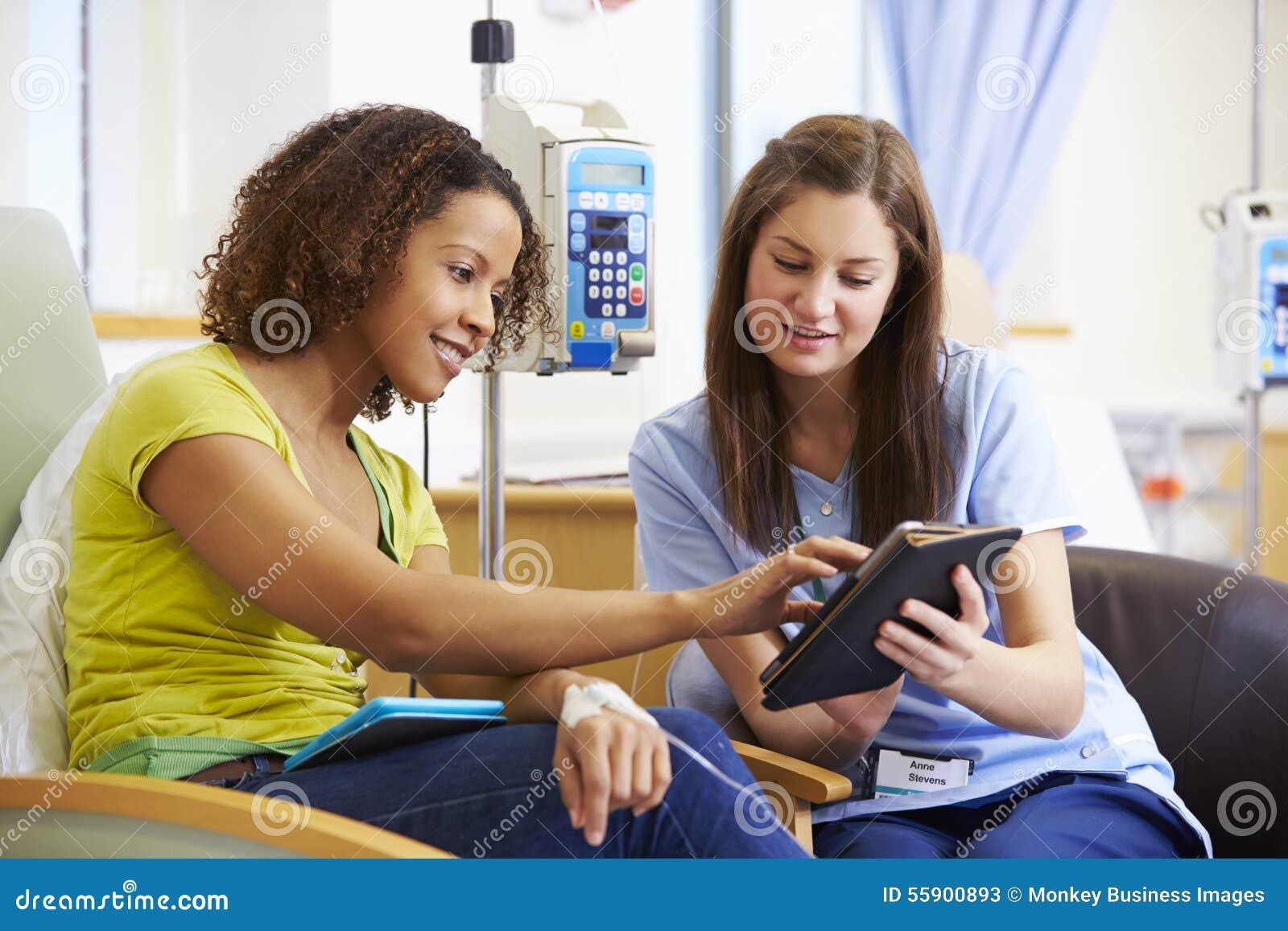 Kvinna som har kemoterapi med sjuksköterskan Using Digital Tablet