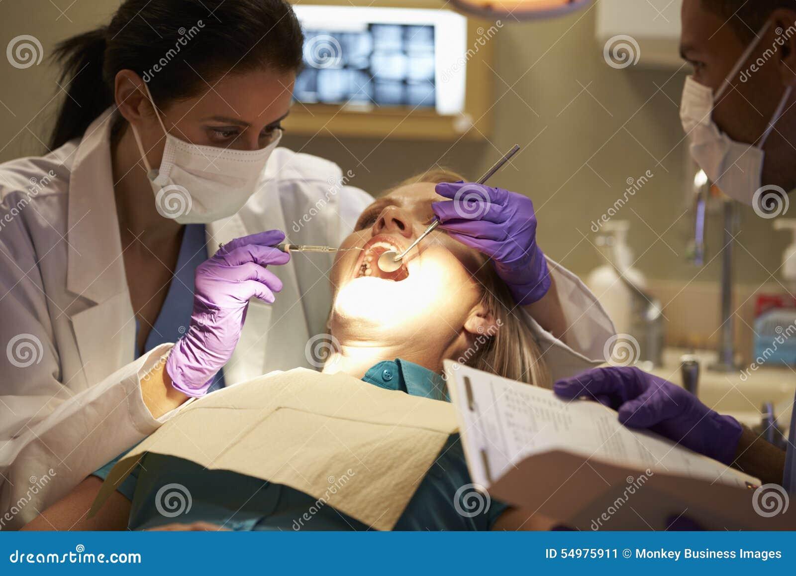 Kvinna som har kontrollen upp på tandläkarekirurgi