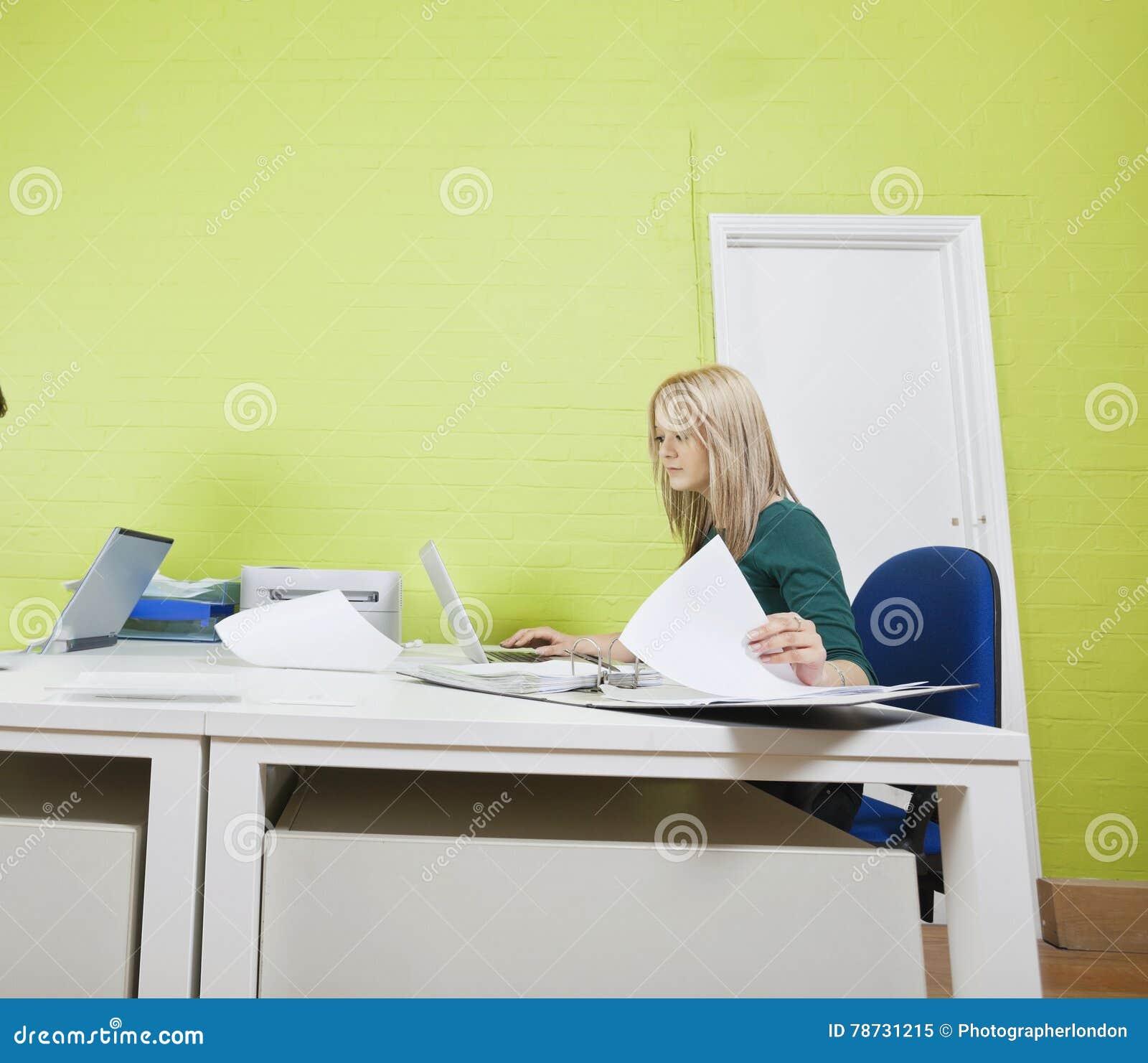 Kvinna som i regeringsställning arbetar mot den gröna väggen