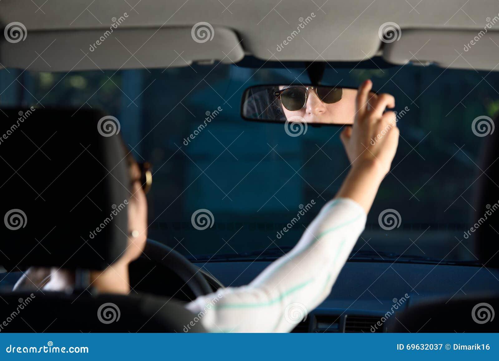 Kvinna som justerar den bakre spegeln