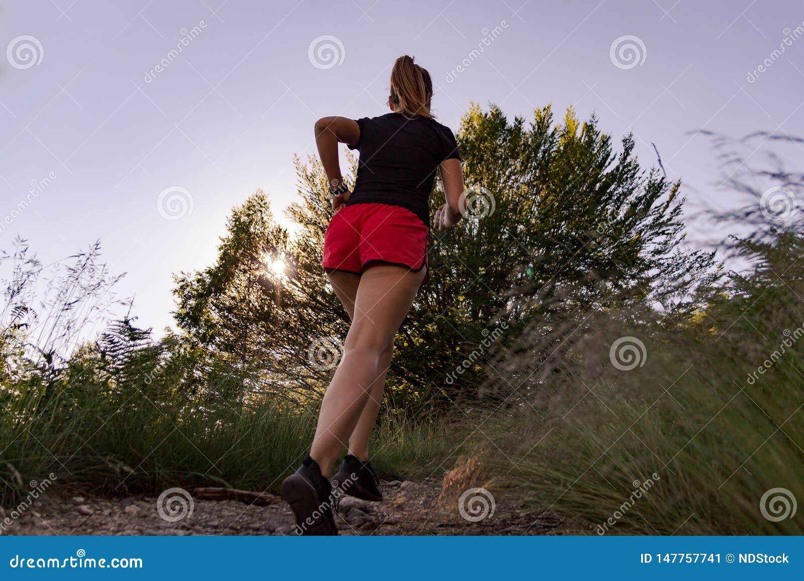 Kvinna som kör i bergen på solnedgången