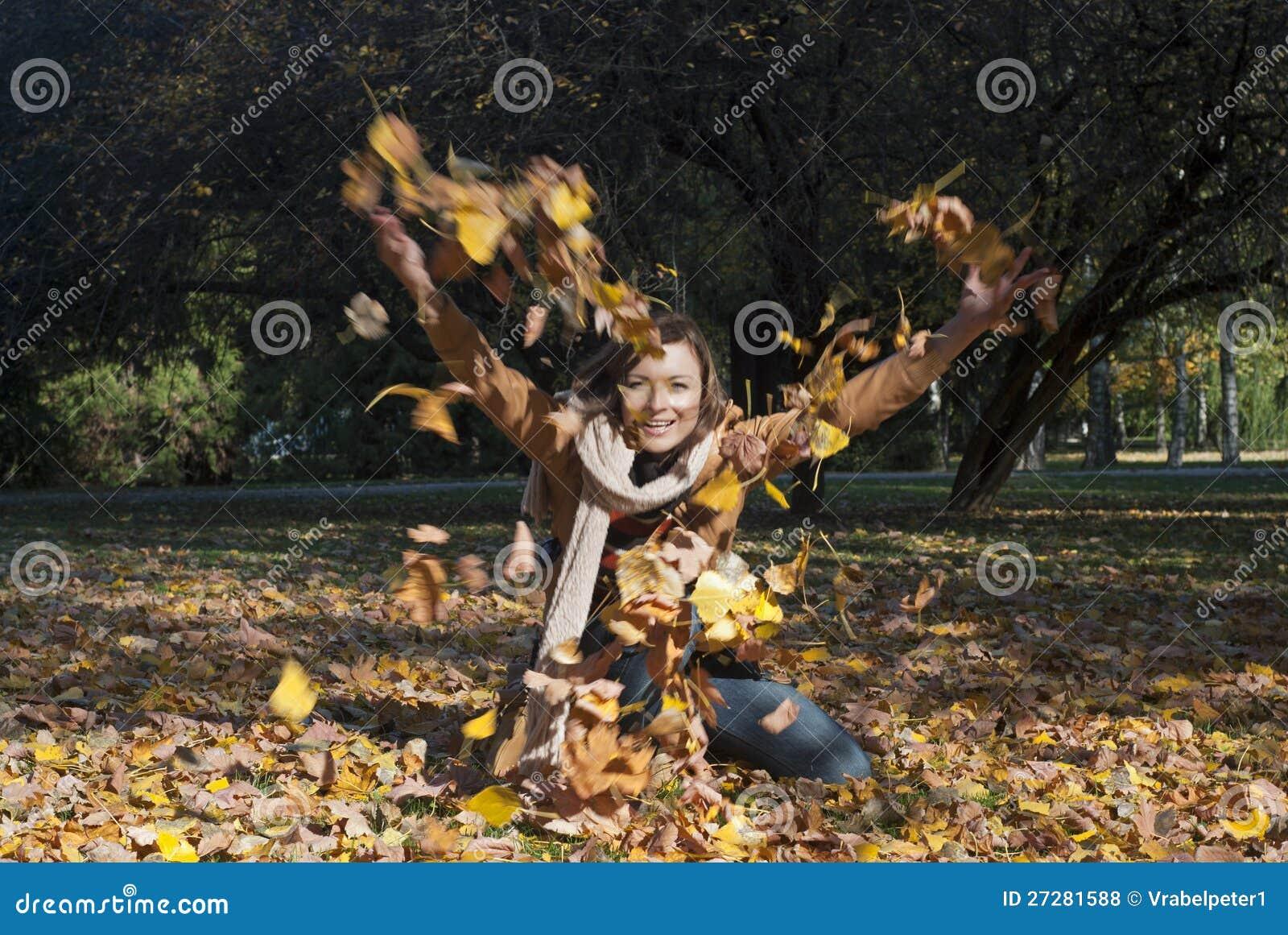 Kvinna som kastar leaves i fall