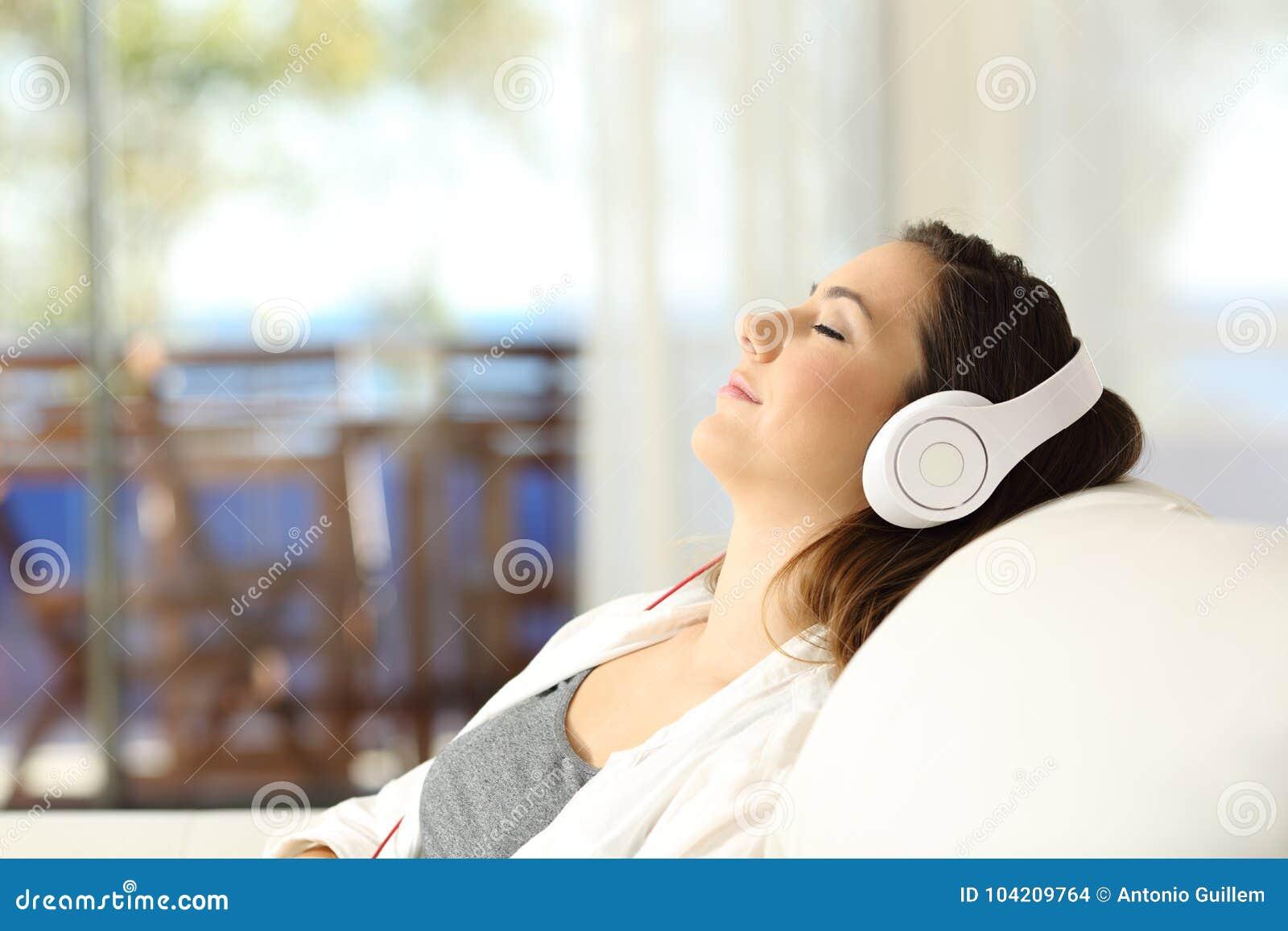 Kvinna som kopplar av att lyssna till musik på en soffa