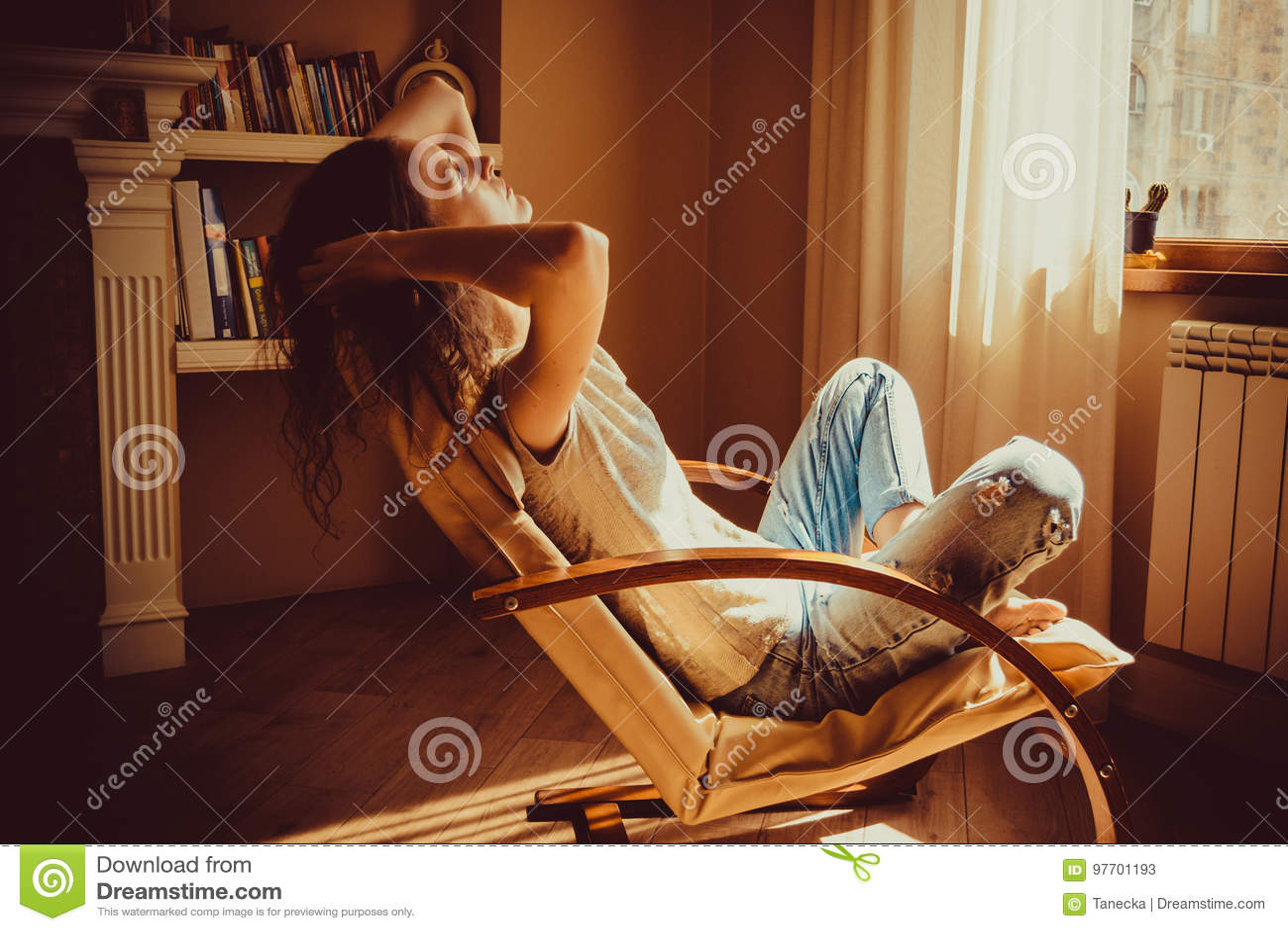 Kvinna som kopplar av efter arbete i bekväm modern stol nära fönster i livingroom Varmt naturligt ljus hemtrevlig utgångspunkt ti