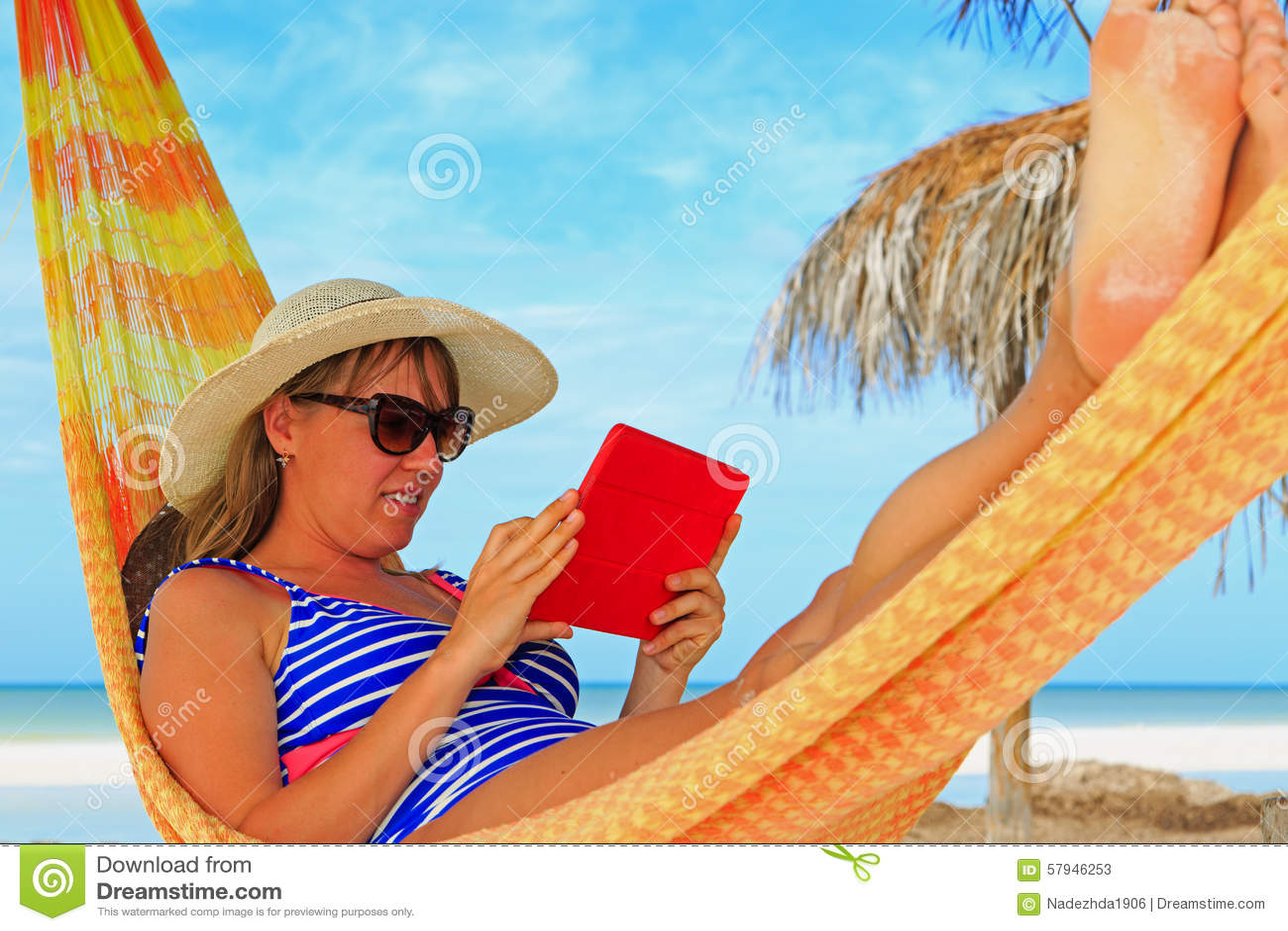 Kvinna som kopplar av i hammockwithhandlagblock på havet