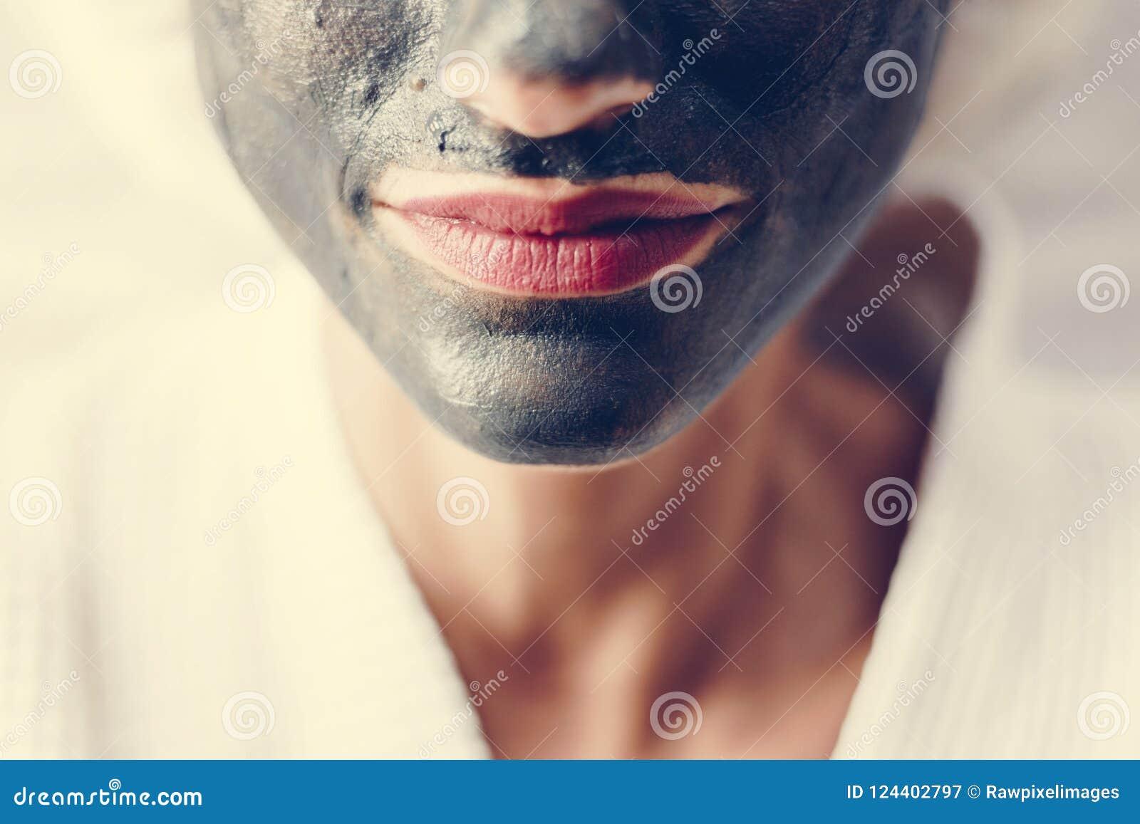 Kvinna som kopplar av med en ansikts- maskering för kol