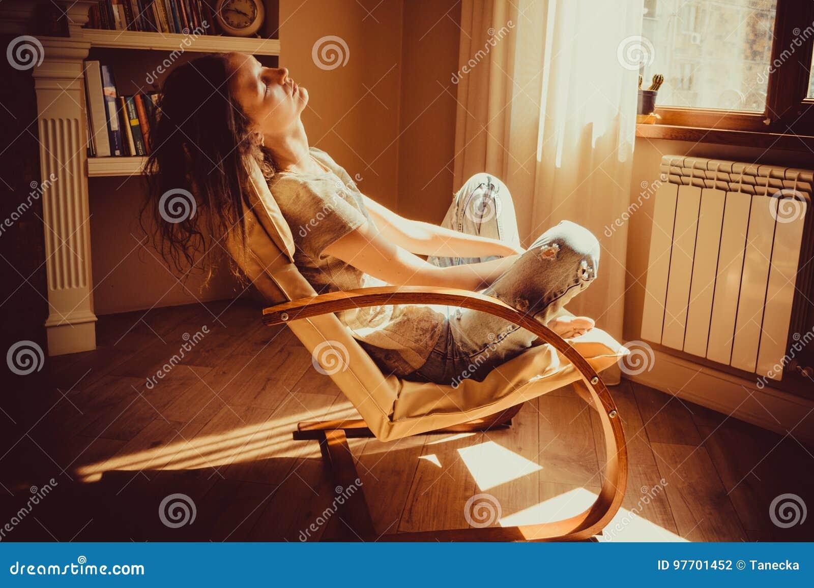 Kvinna som kopplar av och ta sig en tupplur i bekväm modern stol nära fönsterelementet, livingroom Varmt naturligt ljus hemtrevli