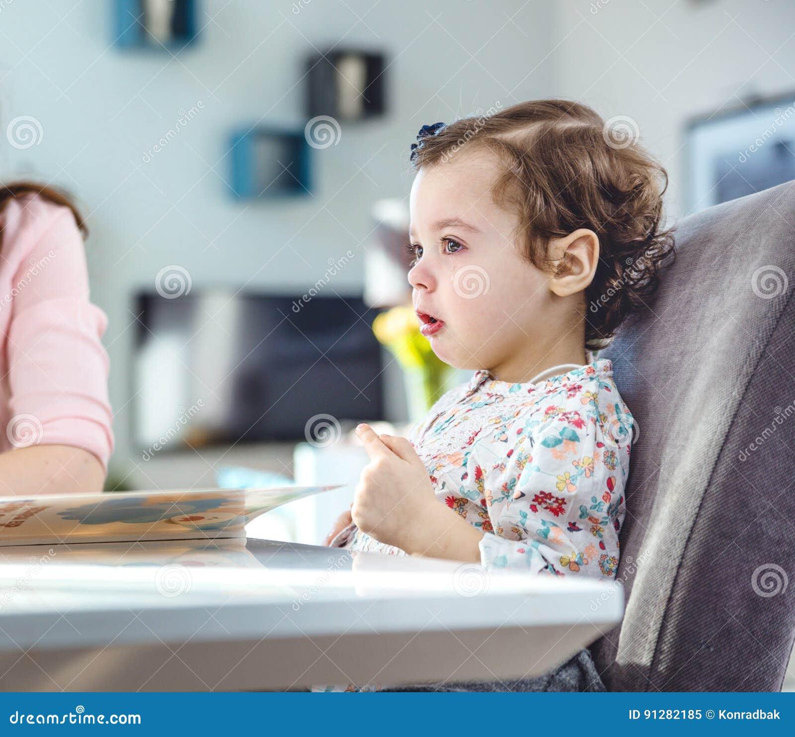 Kvinna som läser en bok till hennes dotter
