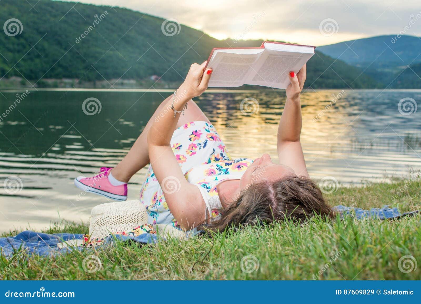 Kvinna som läser en bok vid sjön Solo avkoppling