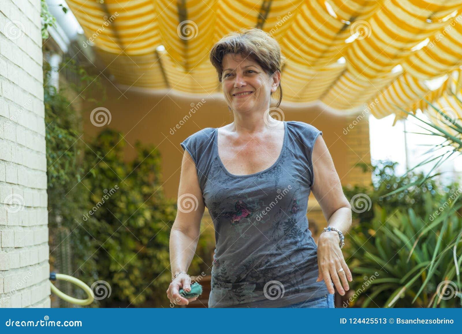 Kvinna som ler, medan gå på hennes terrass