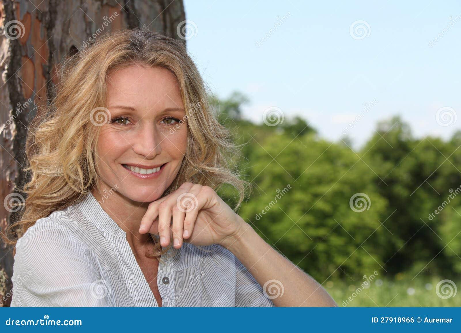 Kvinna som ler under tree