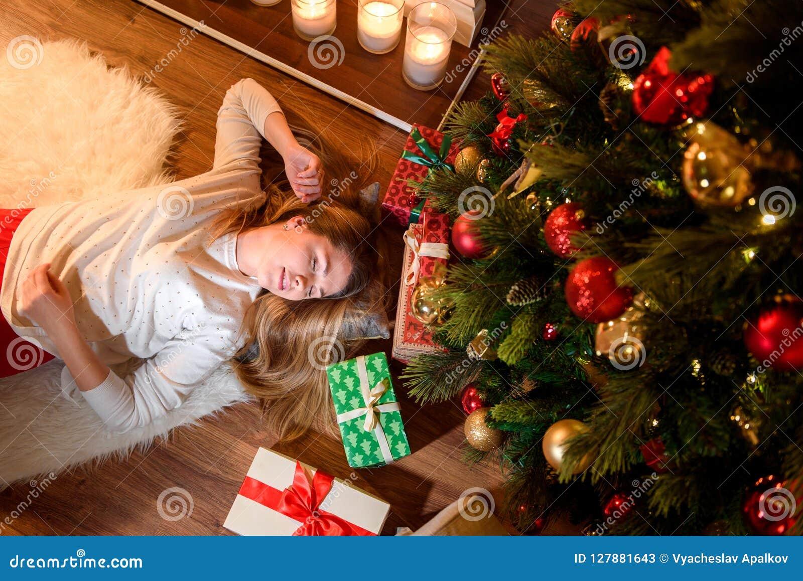 Kvinna som ligger på golvet i jul som hem dekoreras