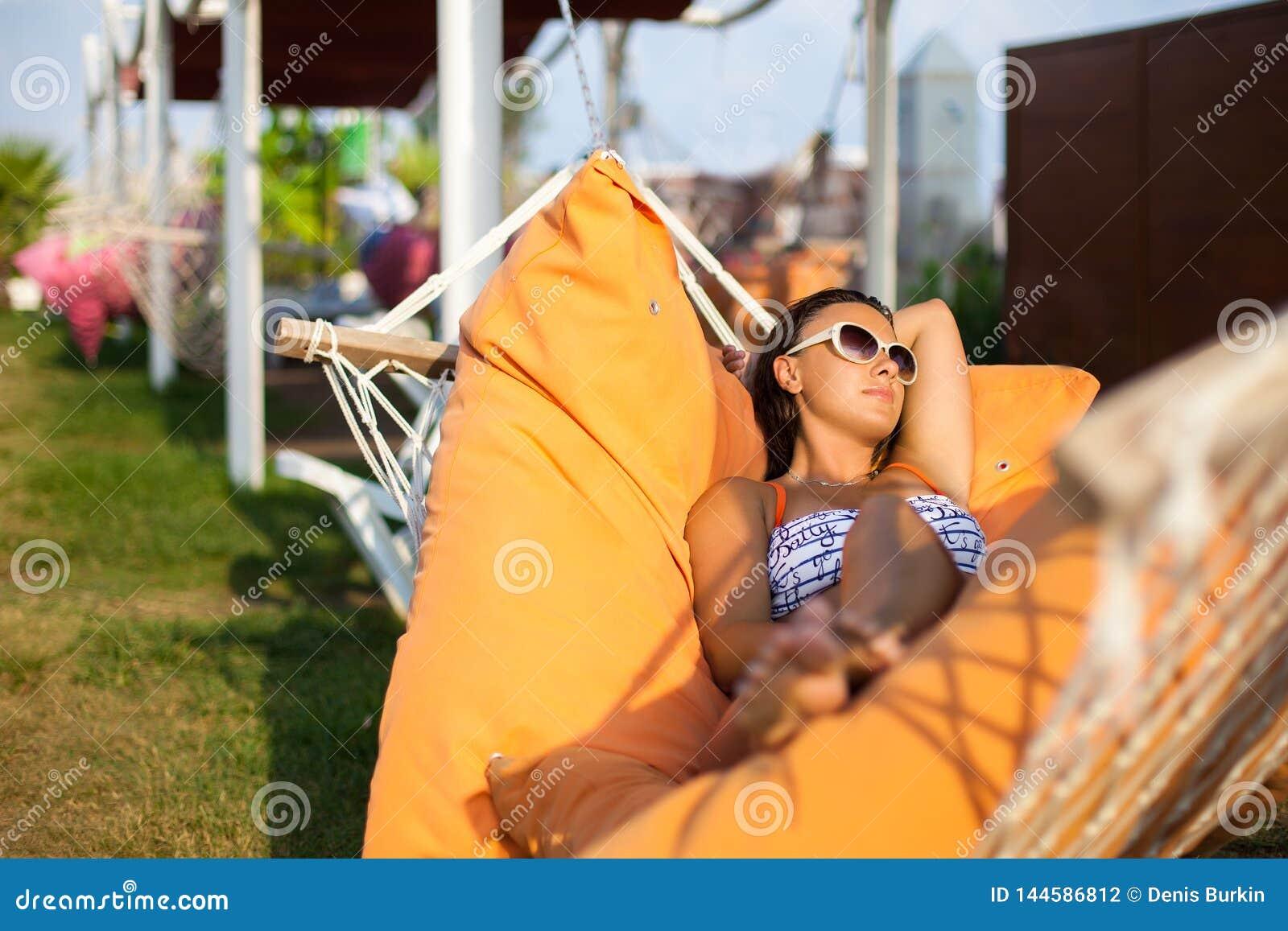 Kvinna som ligger på hängmattan varmt soligt för dag avslappnande kvinna för hängmatta Närbild av en ung lycklig kvinna som ligge