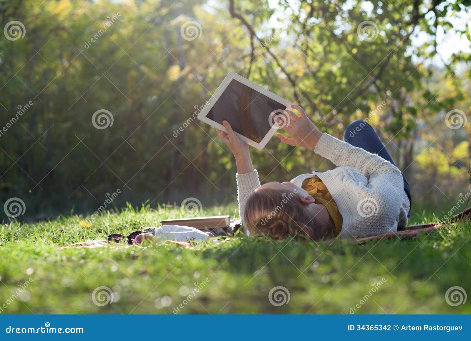 Kvinna som ligger på sängkläder på grönt gräs med ipad