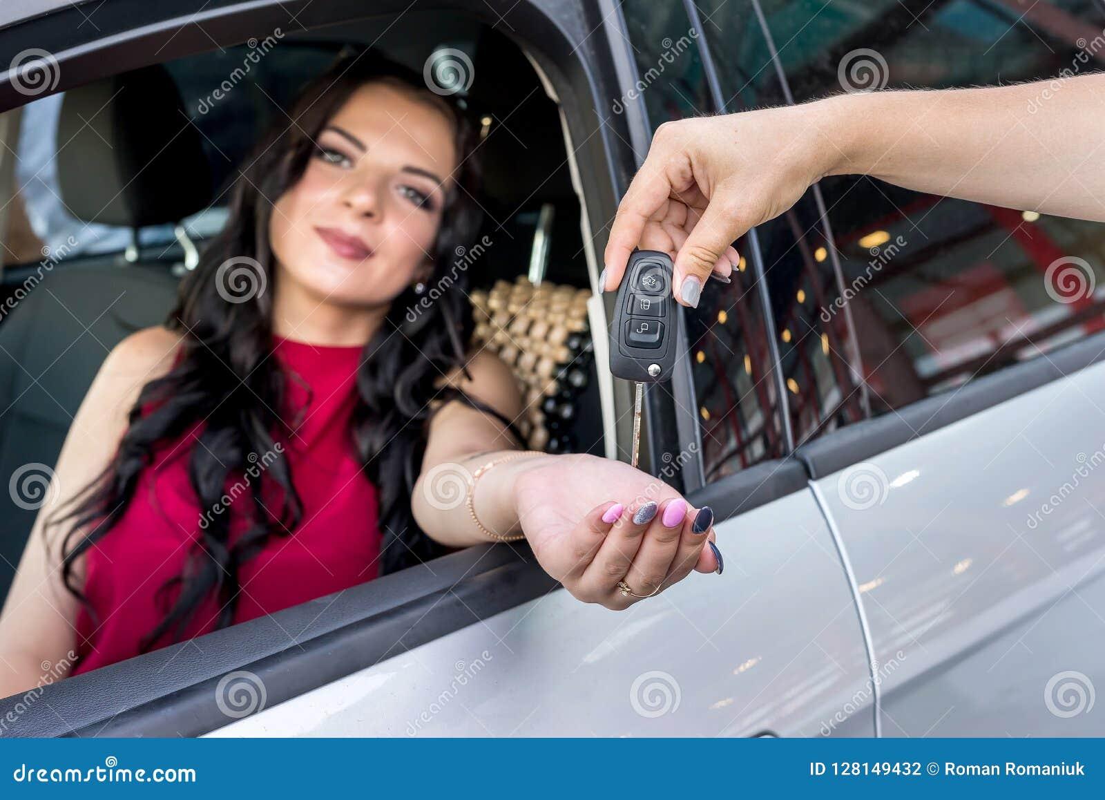 Kvinna som mottar tangenter från en ny bil
