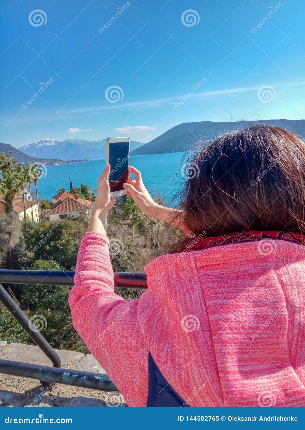 Kvinna som reser den smarta telefonen för bruk och trycker på en mobil skärm på berget och havet