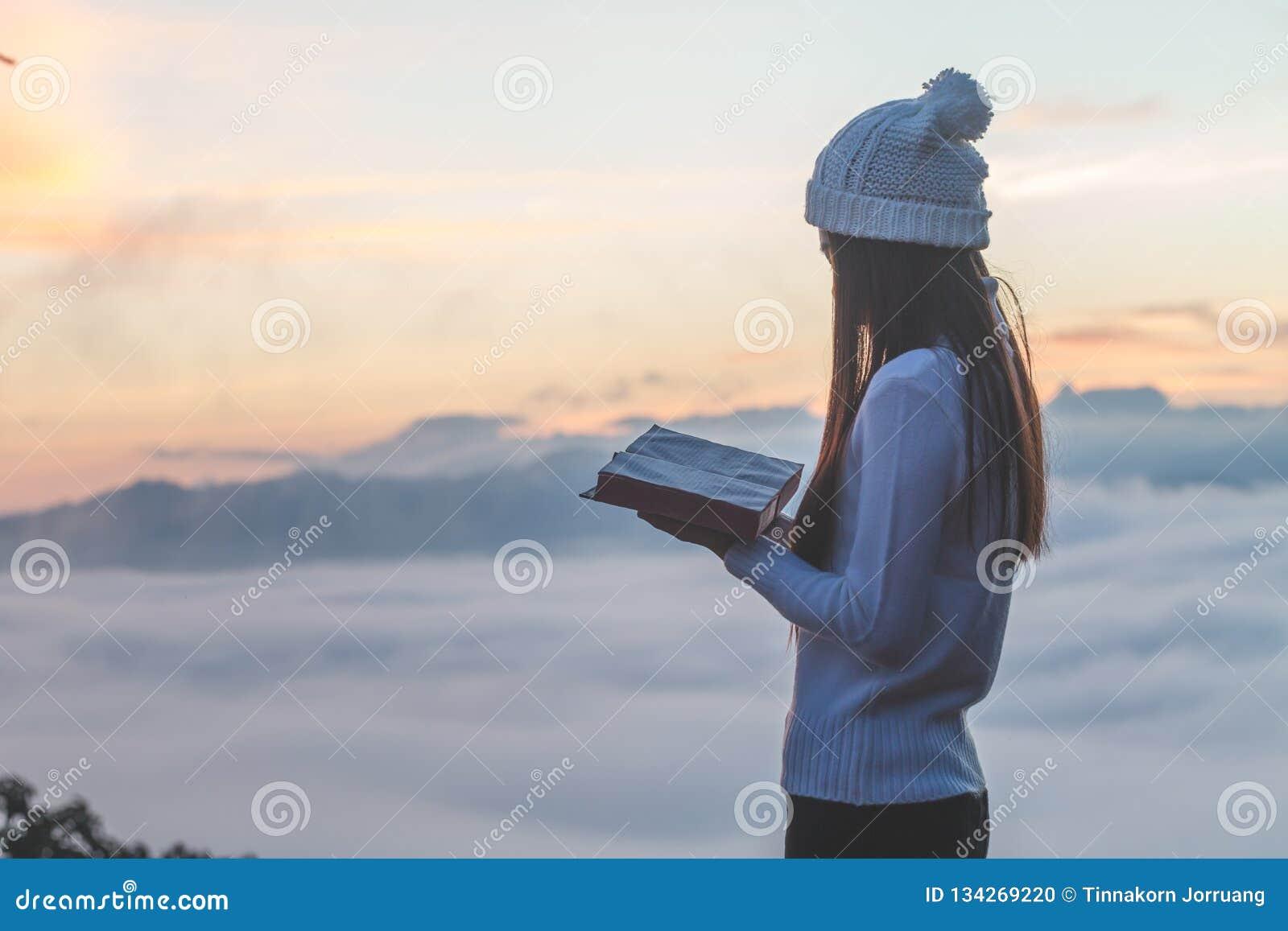 Kvinna som rymmer att läsa bibeln på berget i bilden för morgon