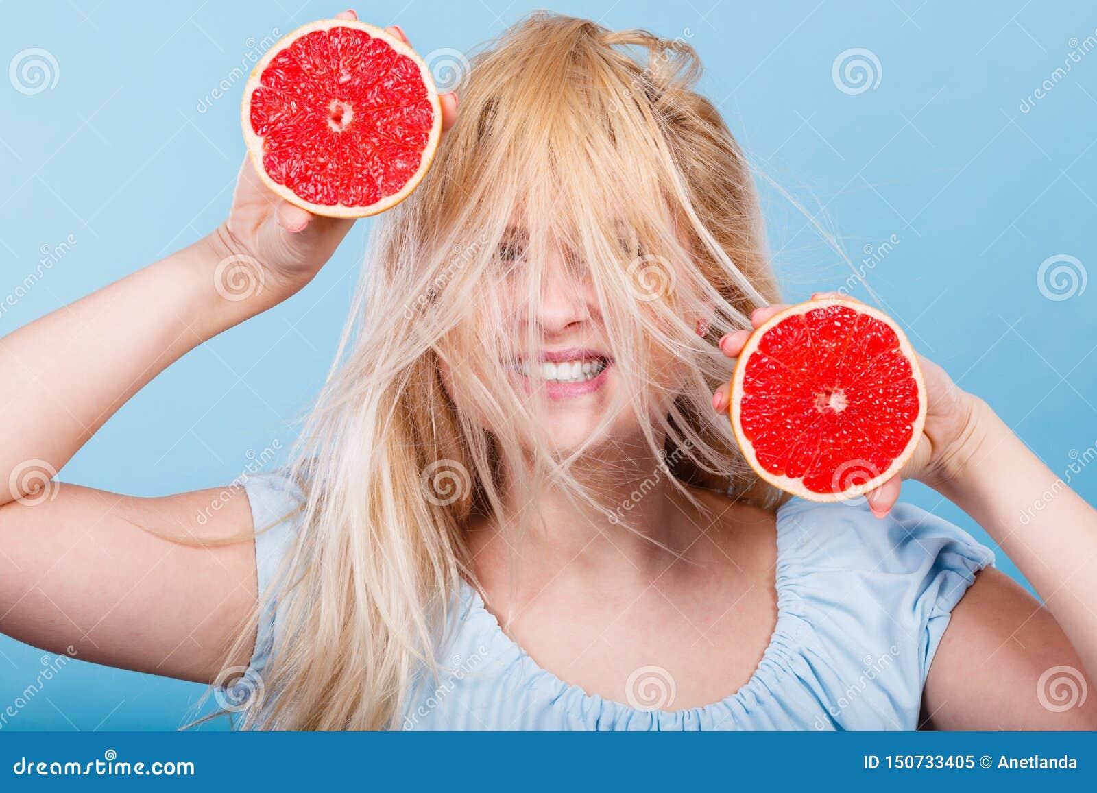 Kvinna som rymmer den r?da grapefrukten som har galet windblown h?r