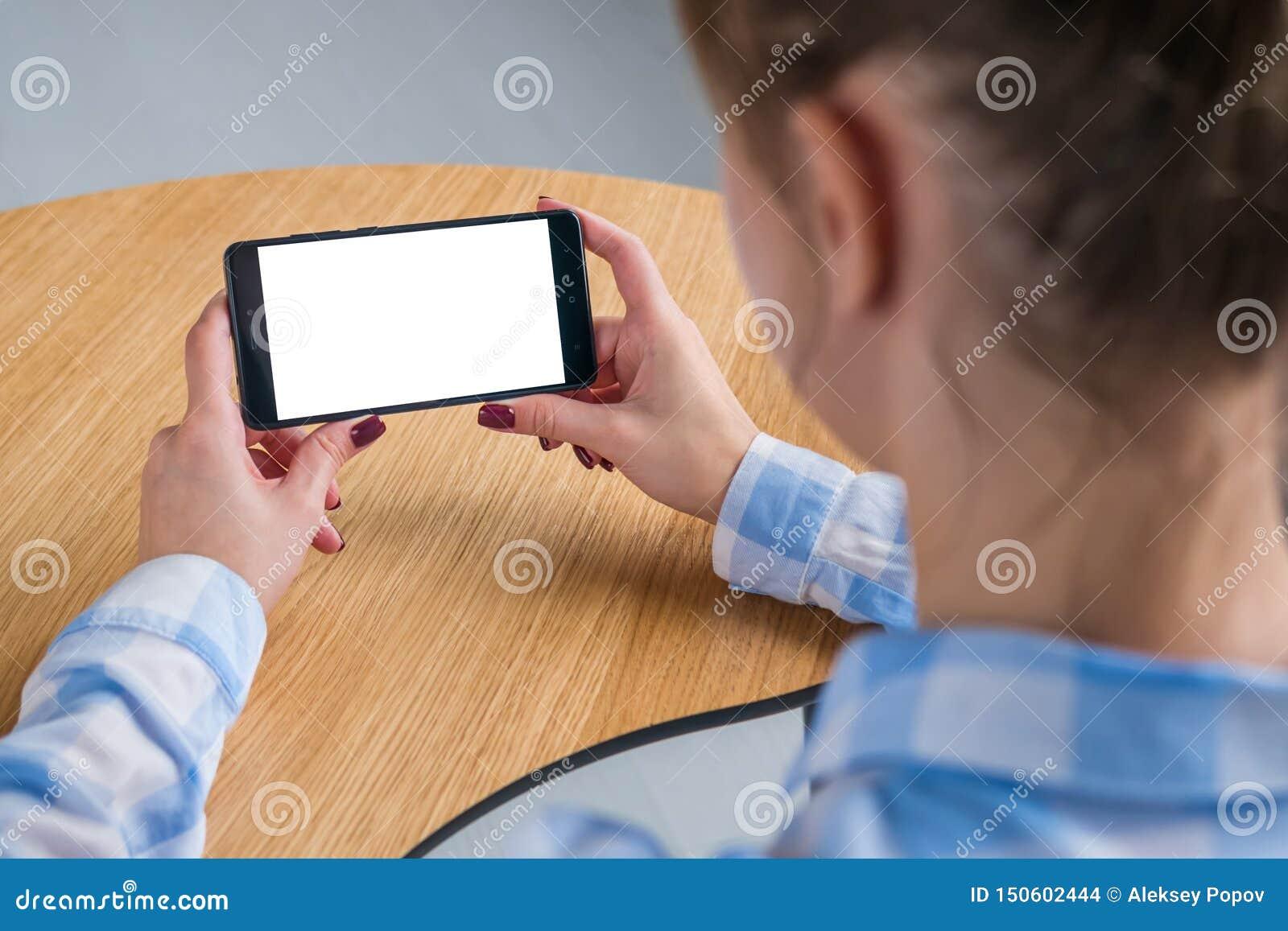 Kvinna som rymmer den svarta smartphonen med den vita tomma sk?rmen - modellbild