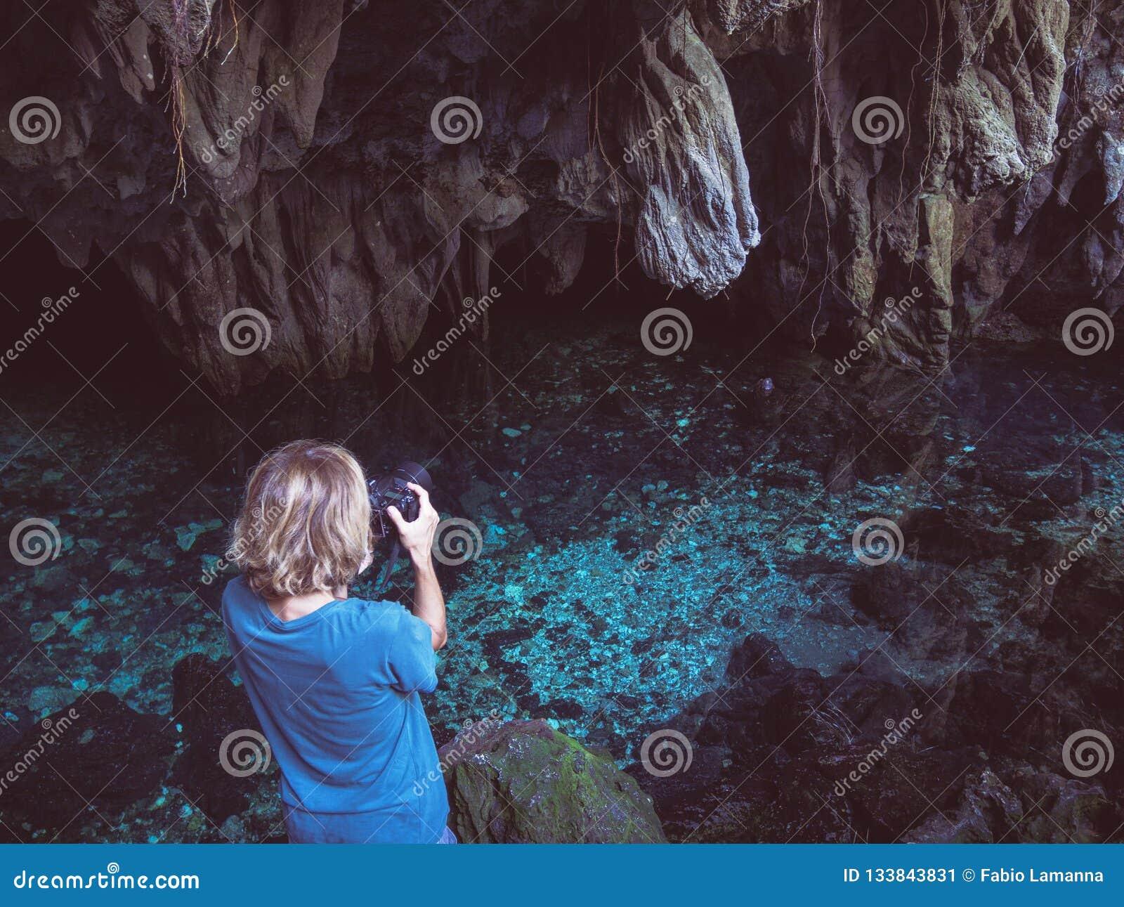 Kvinna som rymmer dlsrkameran som fotograferar den naturliga sjön inom grottan Färgrik reflexion, genomskinligt vatten för turkos