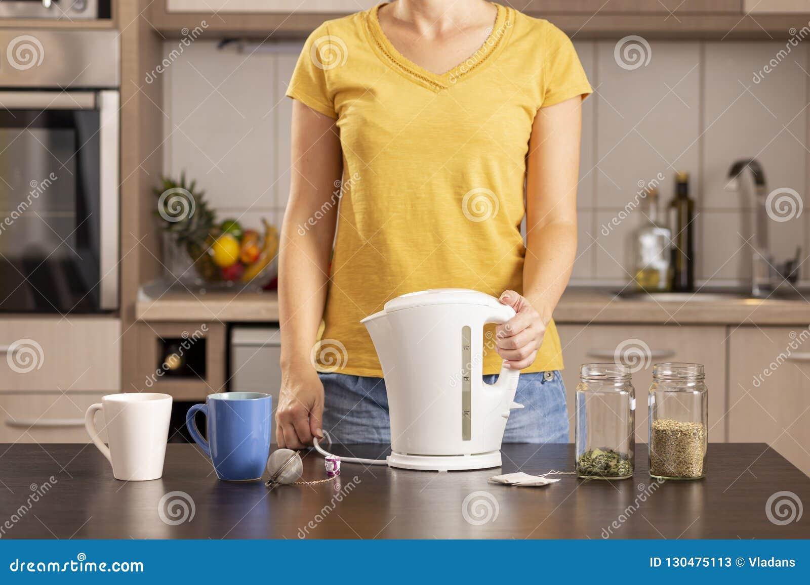 Kvinna som rymmer en kokkärl som gör te