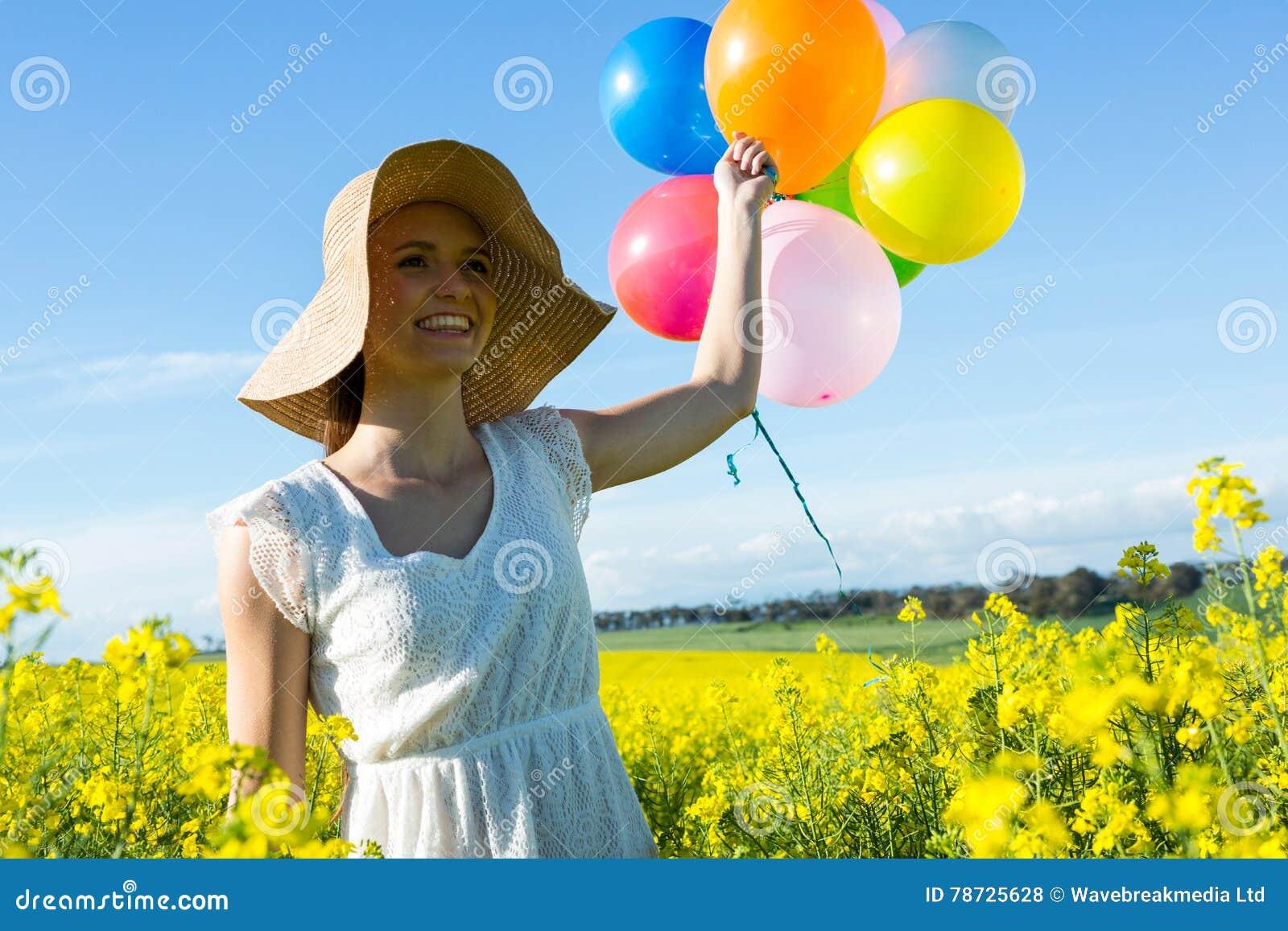 Kvinna som rymmer färgrika ballonger i senapsgult fält