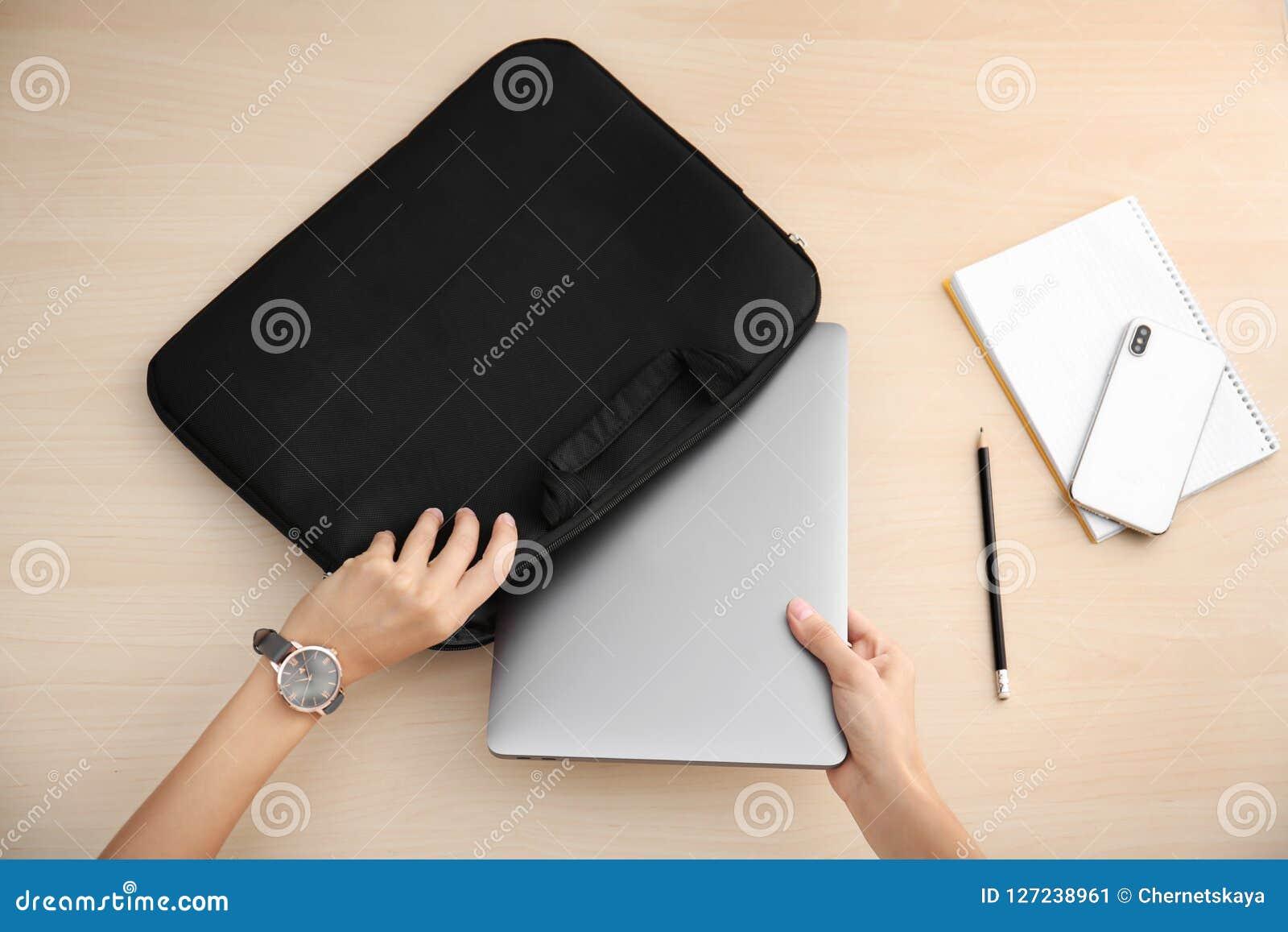 Kvinna som sätter bärbara datorn in i fall på tabellen
