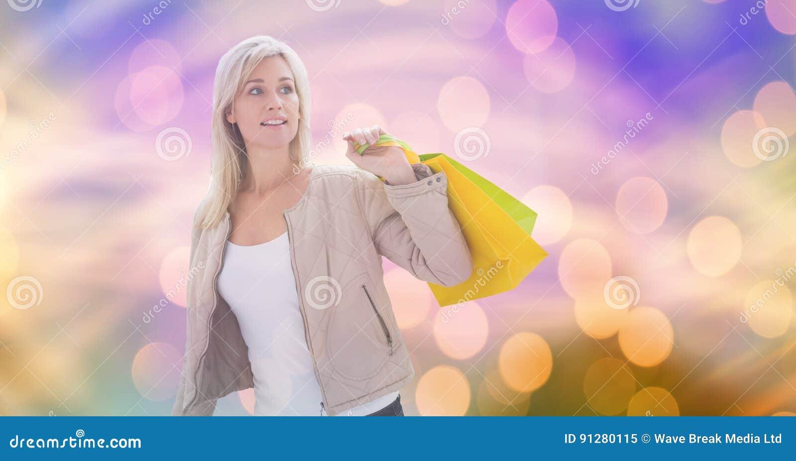 Kvinna som ser bort, medan bära shoppingpåsar över bokeh