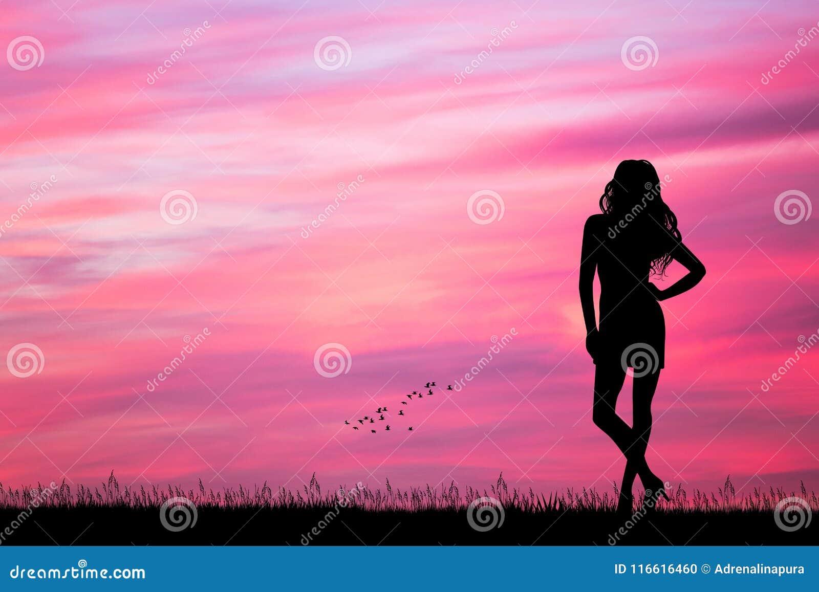 Kvinna som ser den rosa solnedgången