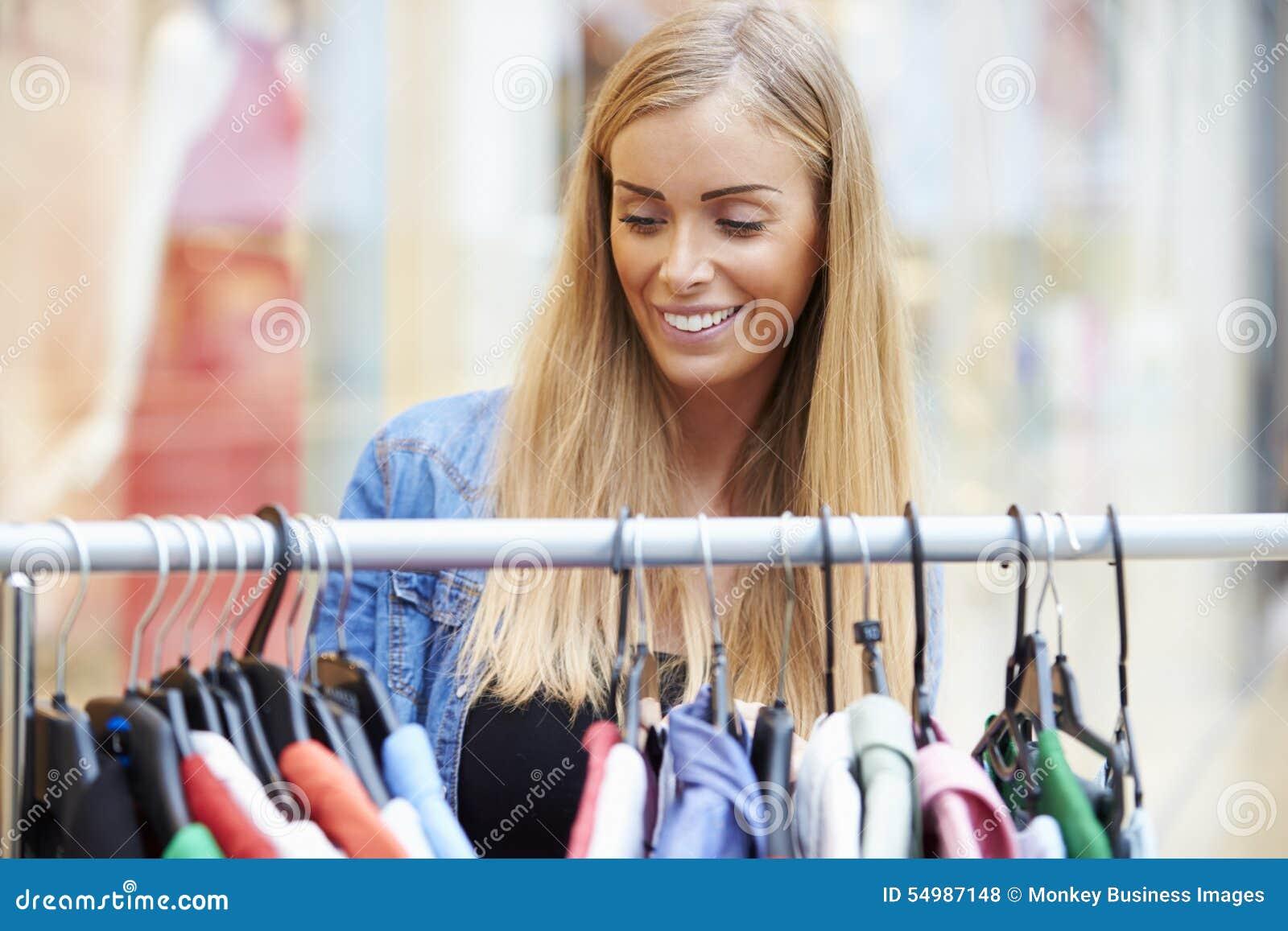 Kvinna som ser kläder på stången i shoppinggalleria