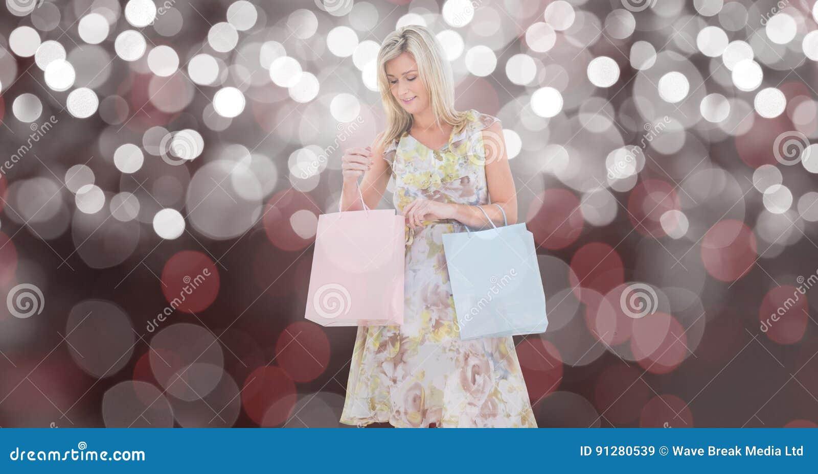 Kvinna som ser shoppingpåsen över suddighetsbakgrund